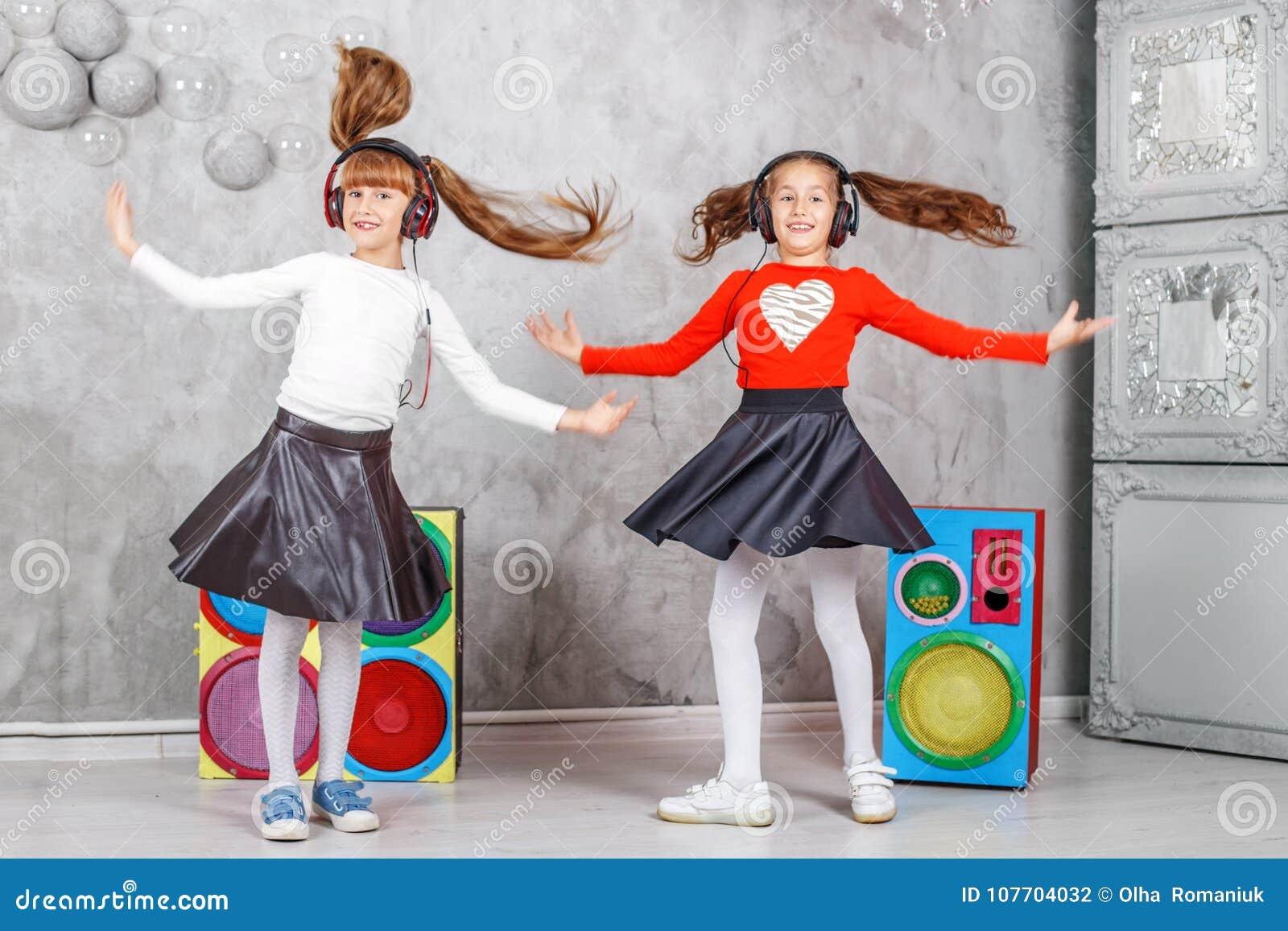Lyckliga barn dansar och lyssnar till musik i hörlurar Det conc