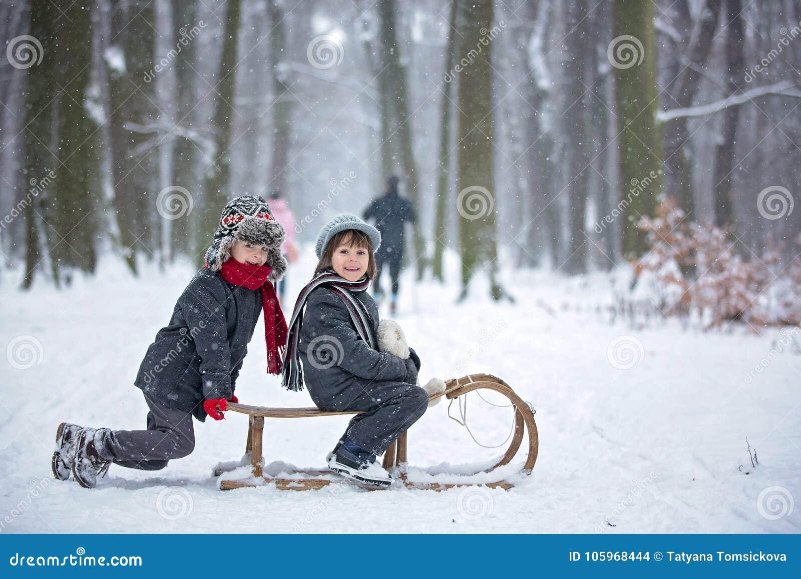 Lyckliga barn i en vinter parkerar och att spela samman med en pulka
