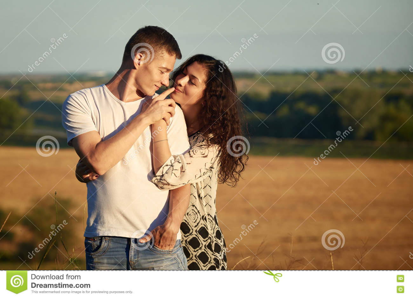 Lyckliga barnpar som poserar höjdpunkt på det utomhus- over gula fältet för land, romantiskt folkbegrepp, sommarsäsong