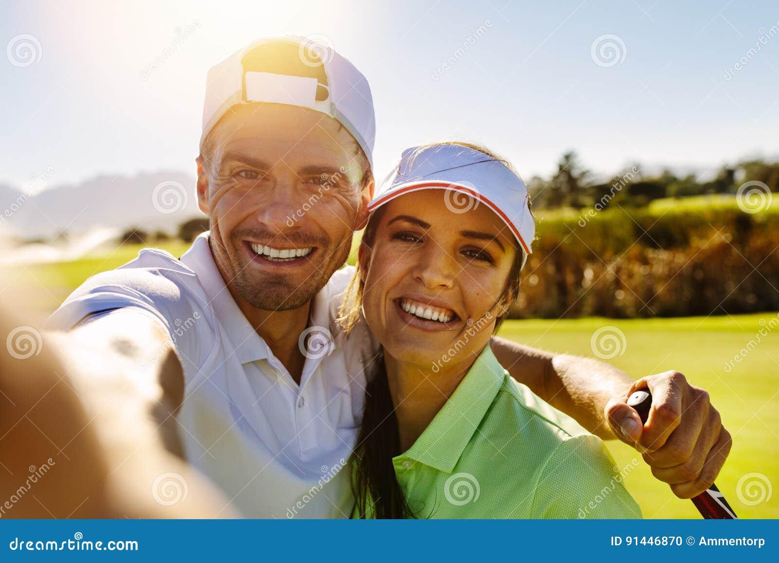 Lyckliga barnpar som tar selfie på golfbanan