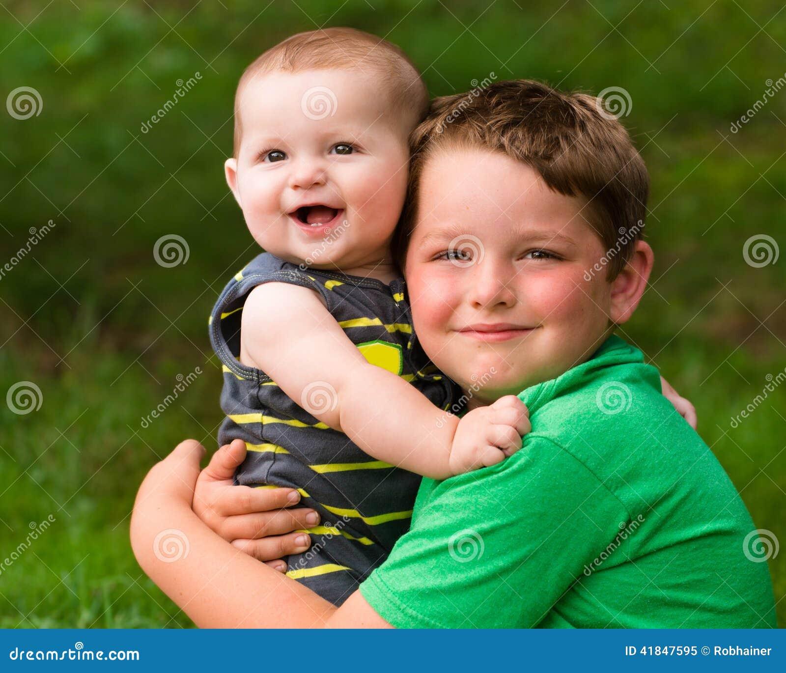 Lyckliga bröder som kramar i sommarstående