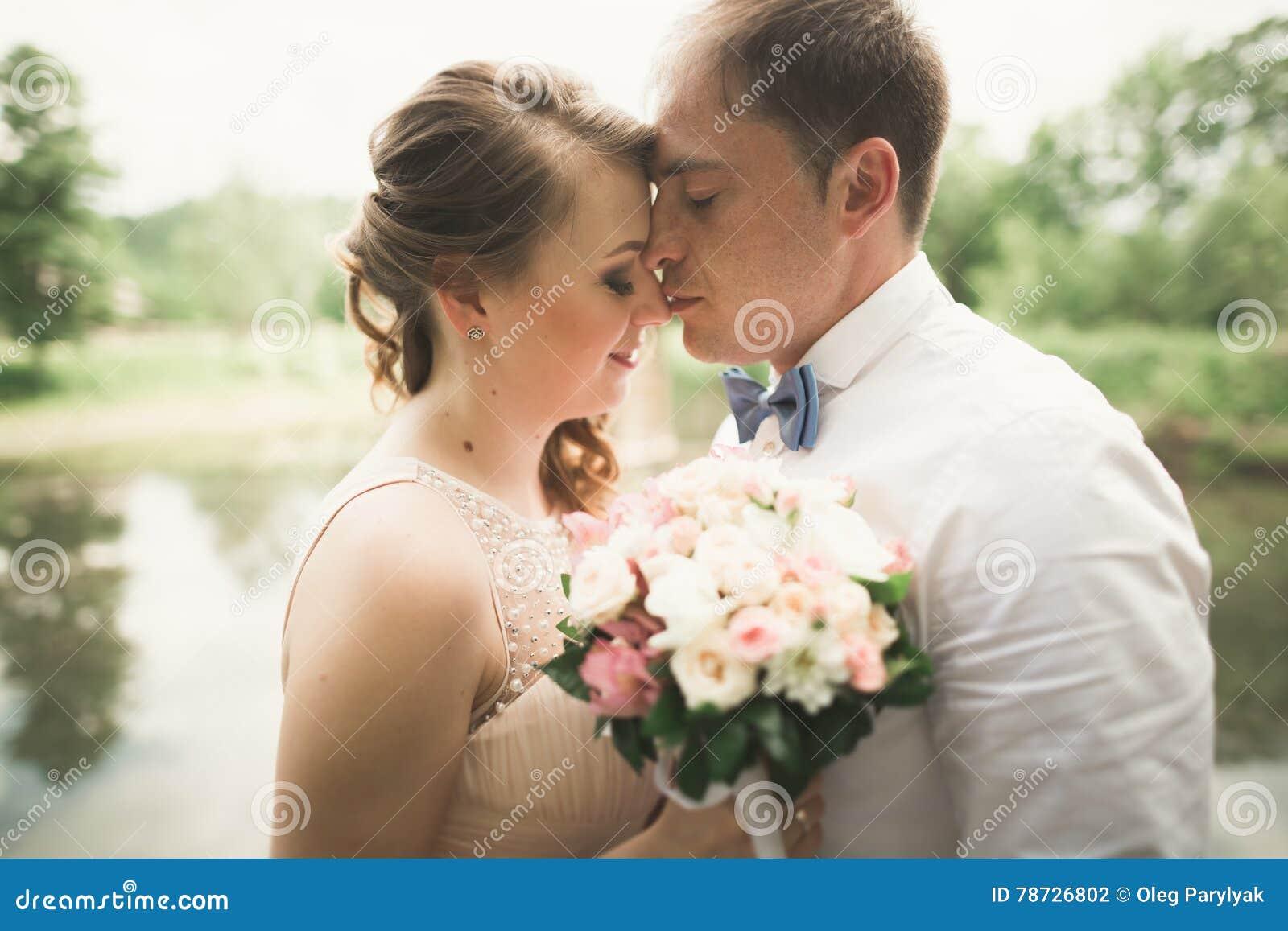 Lyckliga brölloppar som kramar och ler sig på bakgrundssjön, skog