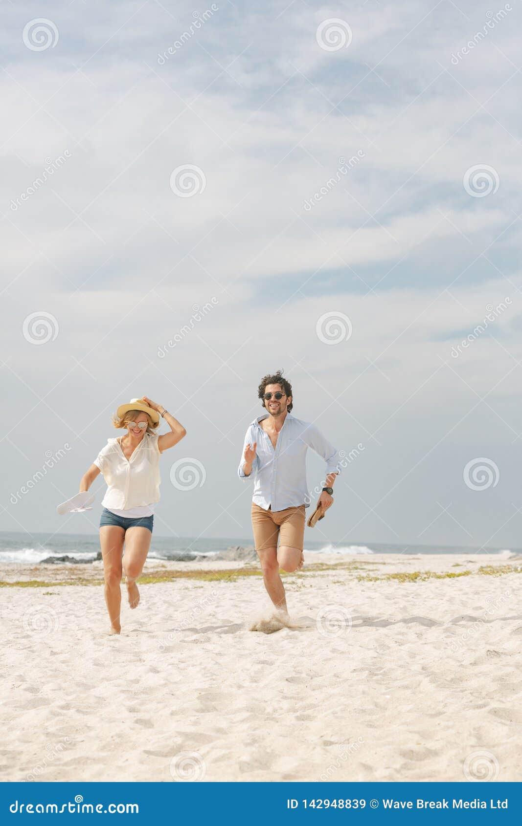 Lyckliga Caucasian par som kör på stranden på solig dag