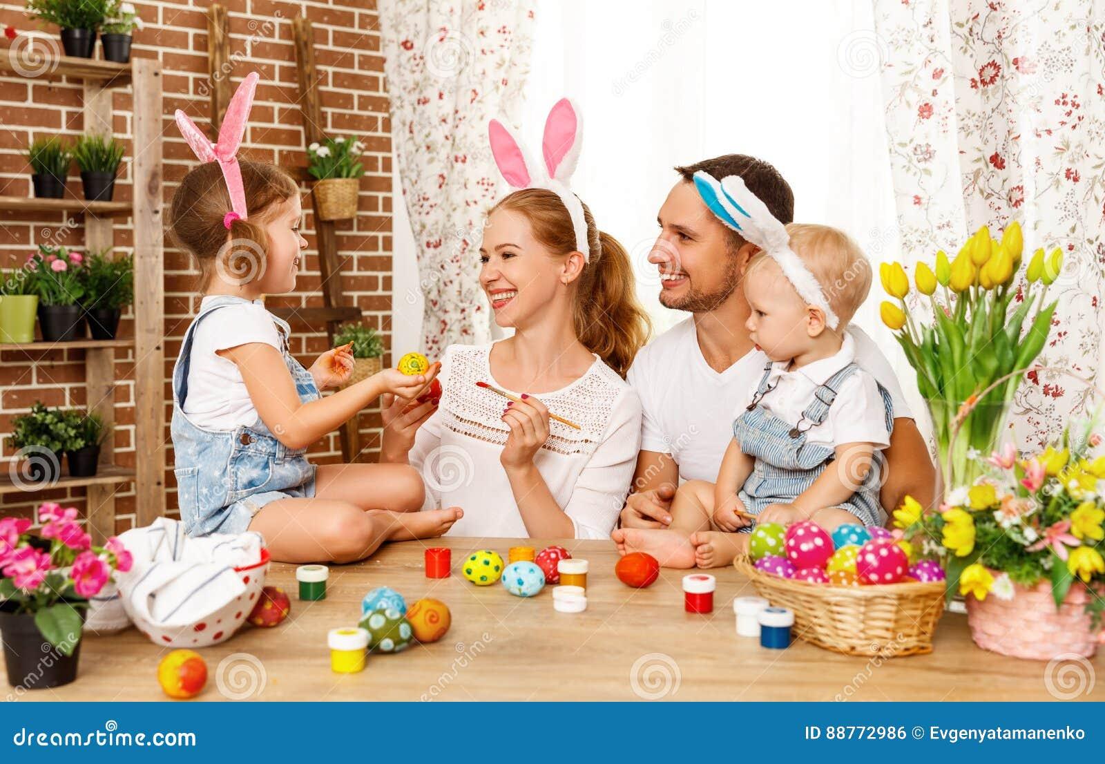 Lyckliga easter! den familjmodern, fadern och barn målar ägg för