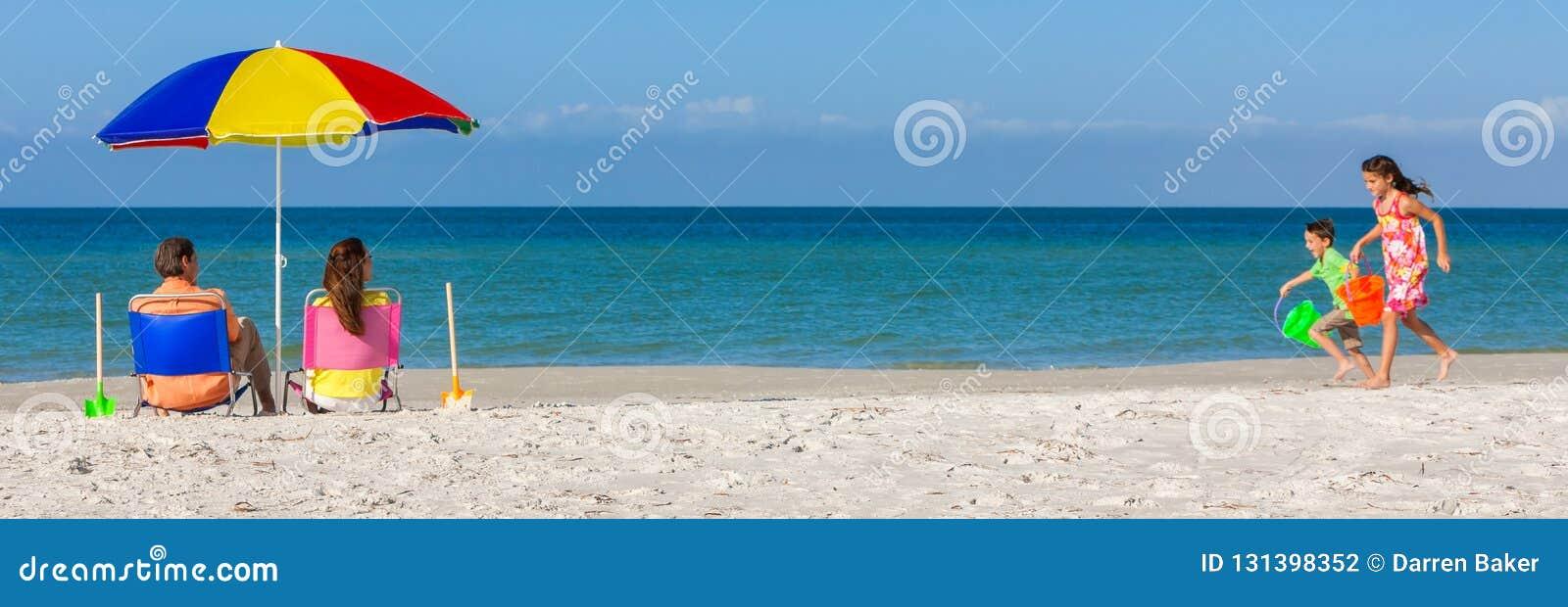 Lyckliga familjföräldrar och barn som har gyckel i solstolar på en strand