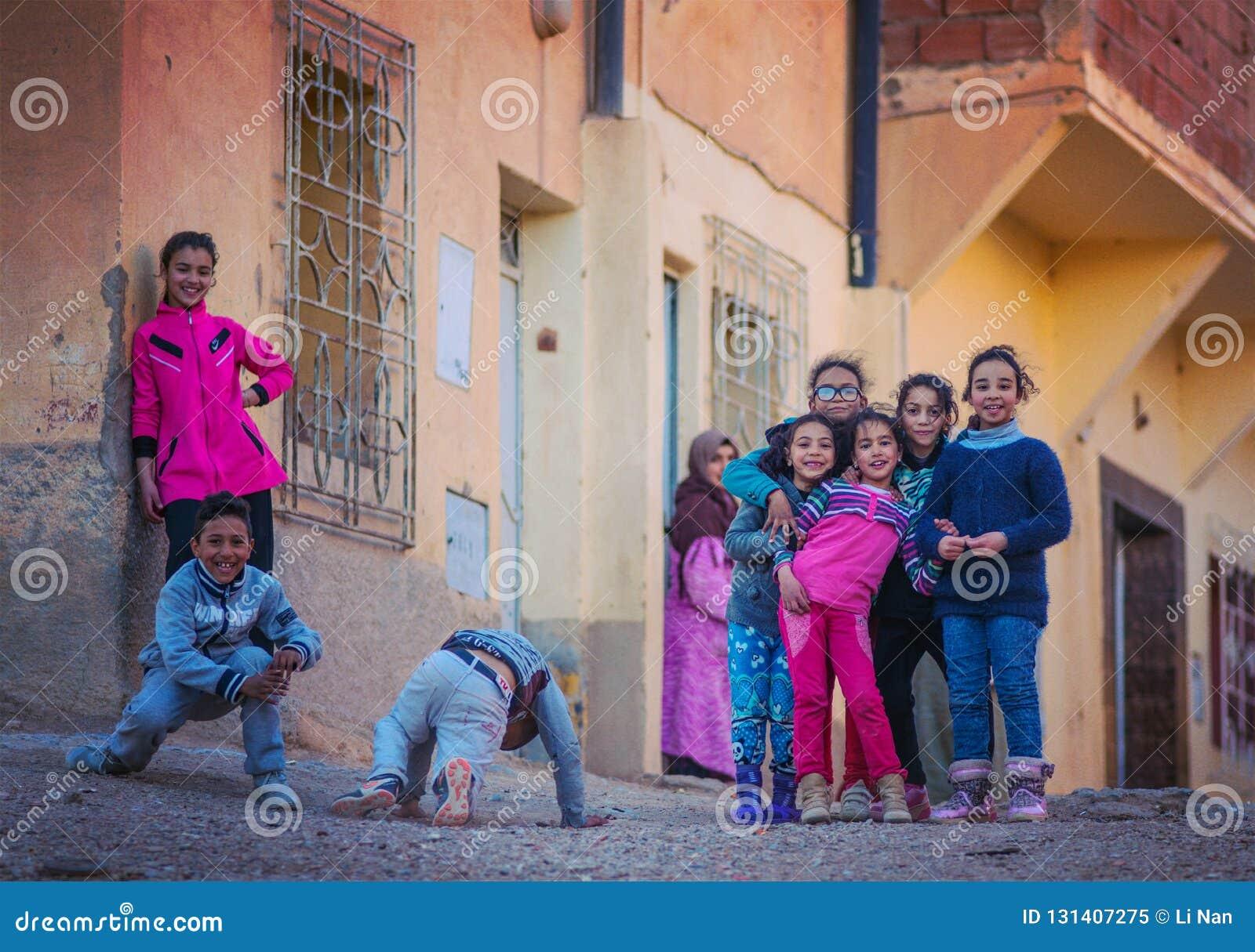 Lyckliga fattiga vänliga barn flicka och pojke i den Marocko byn med det gamla huset