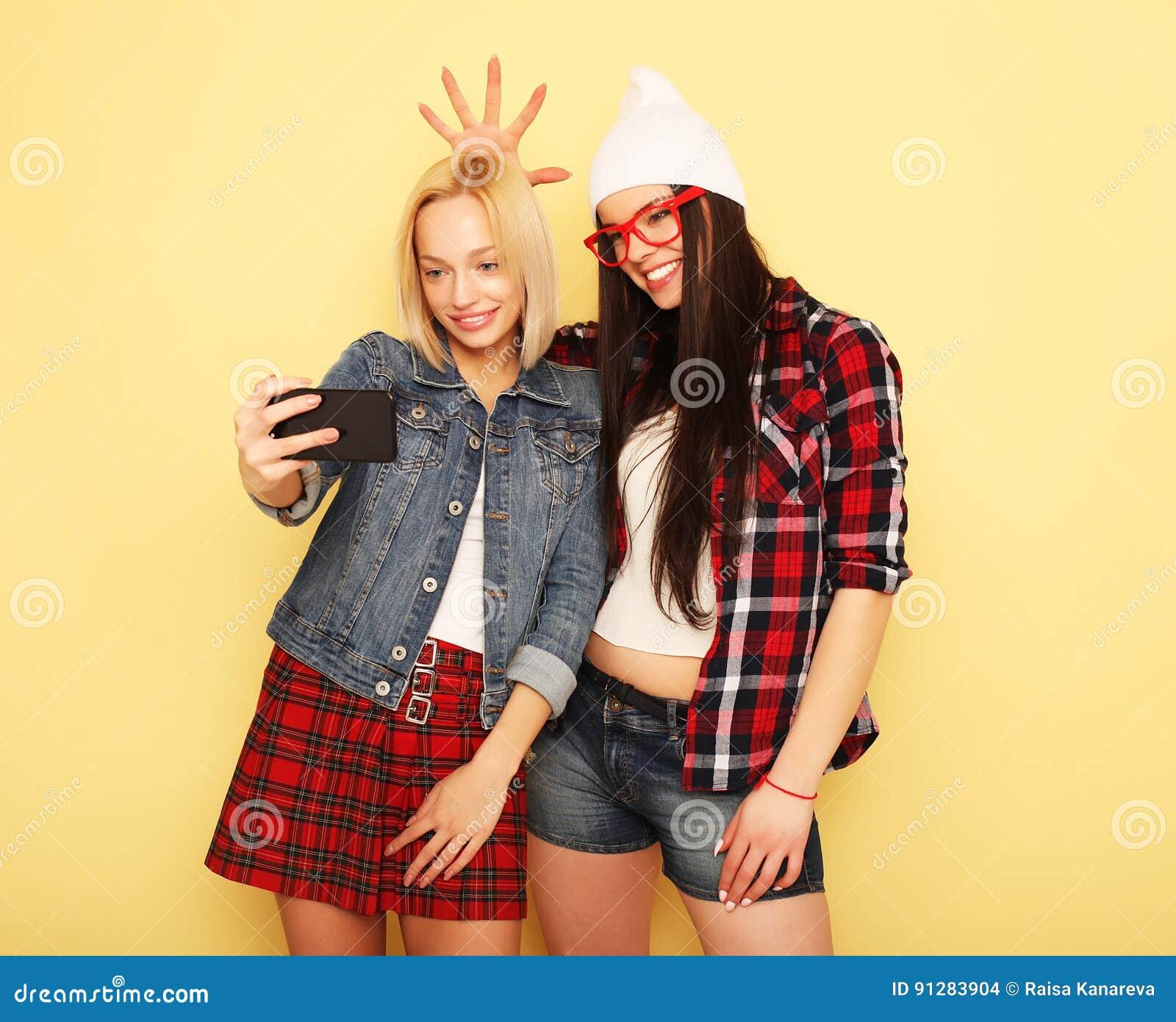 Lyckliga flickor med smartphonen över gul bakgrund Lycklig själv
