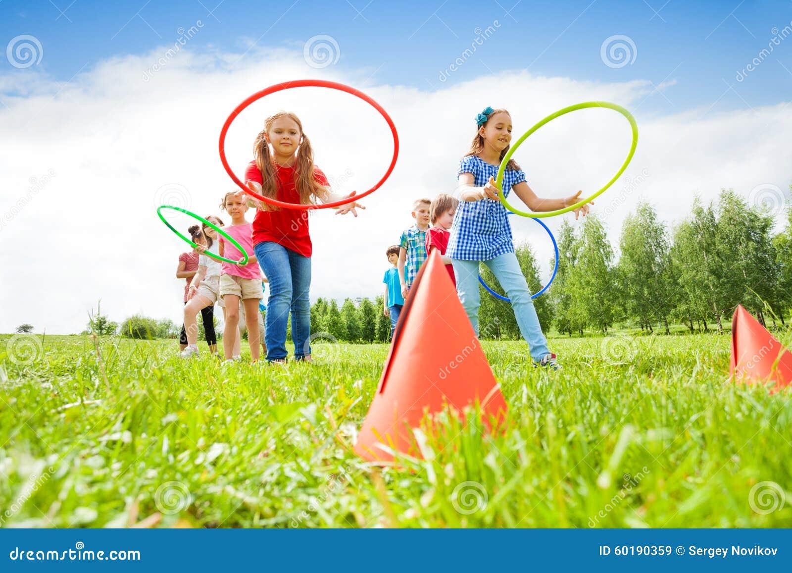 Lyckliga flickor och pojkar som kastar färgrika beslag