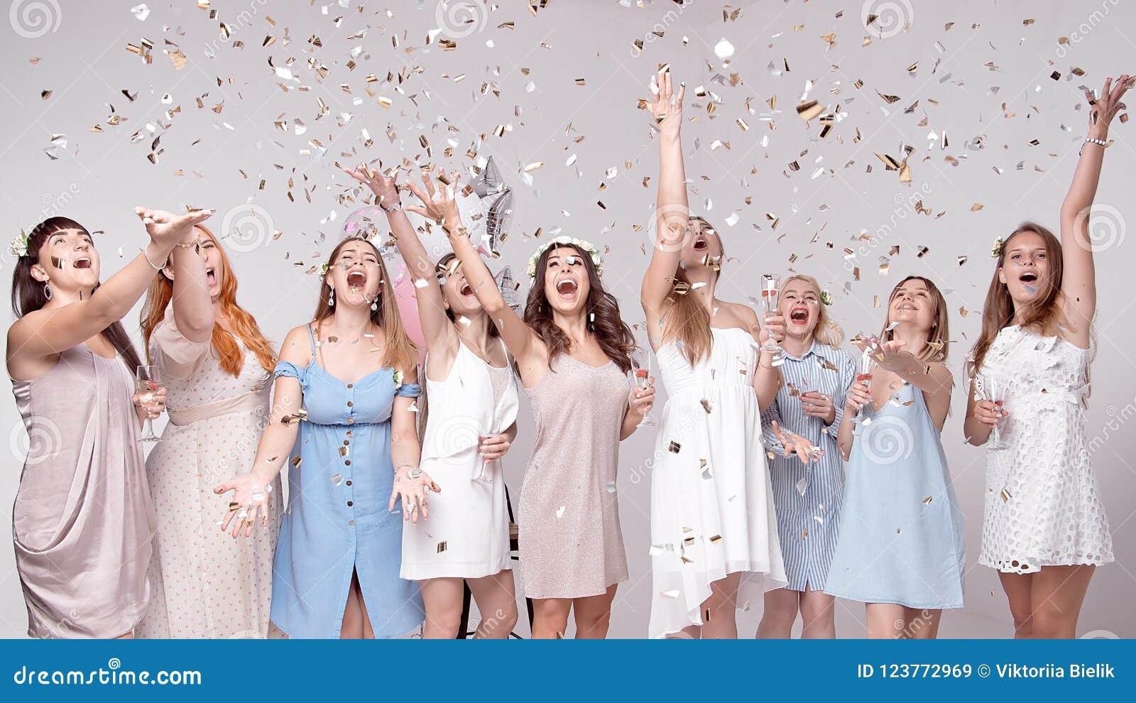 Lyckliga flickor som har gyckel som dricker med champagne på partiet Begrepp av uteliv, ungmöparti, möhippa