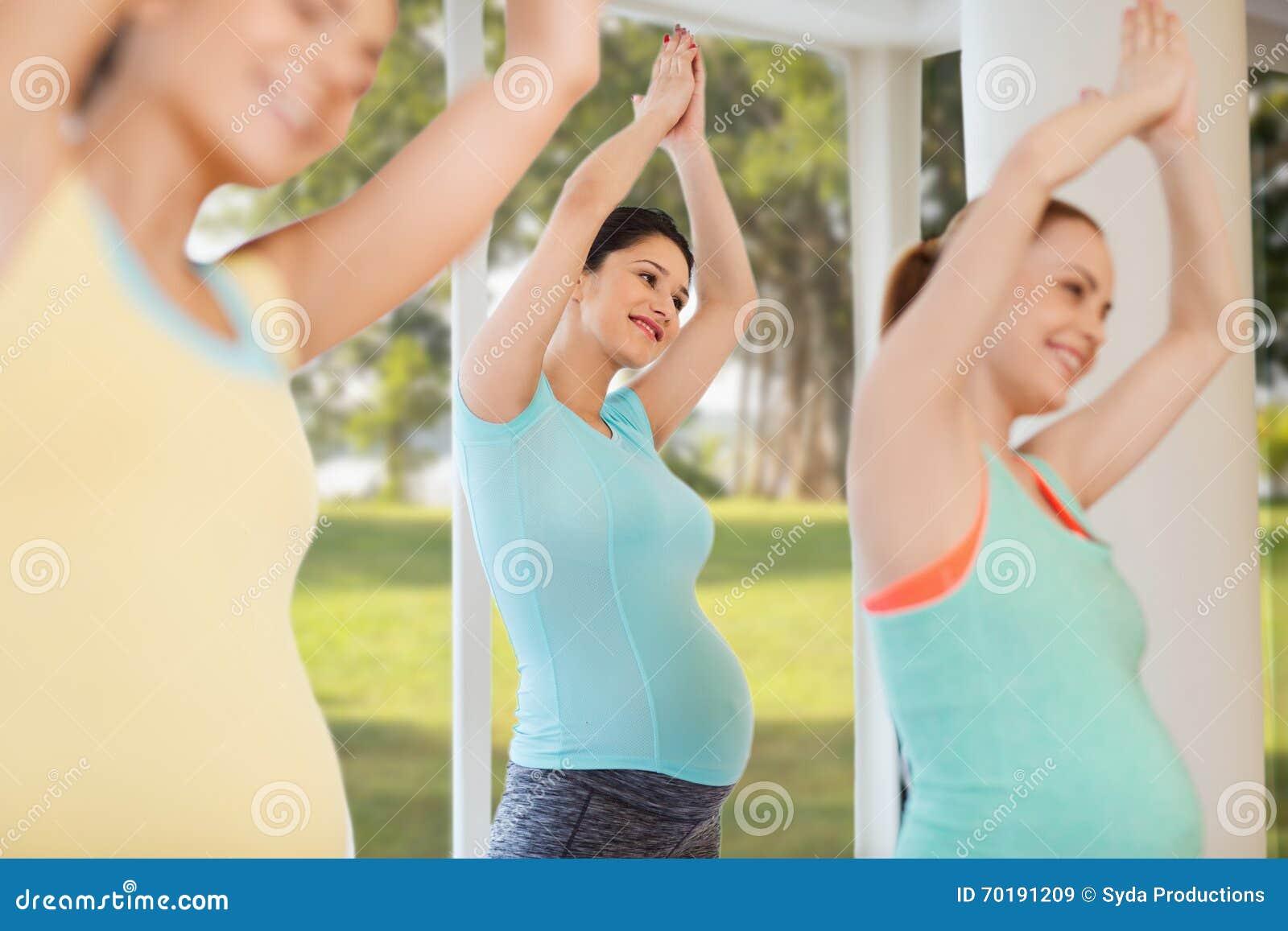 Lyckliga gravida kvinnor som övar i idrottshall