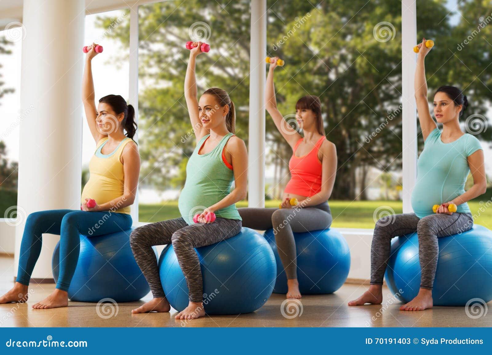Lyckliga gravida kvinnor som övar på fitball i idrottshall