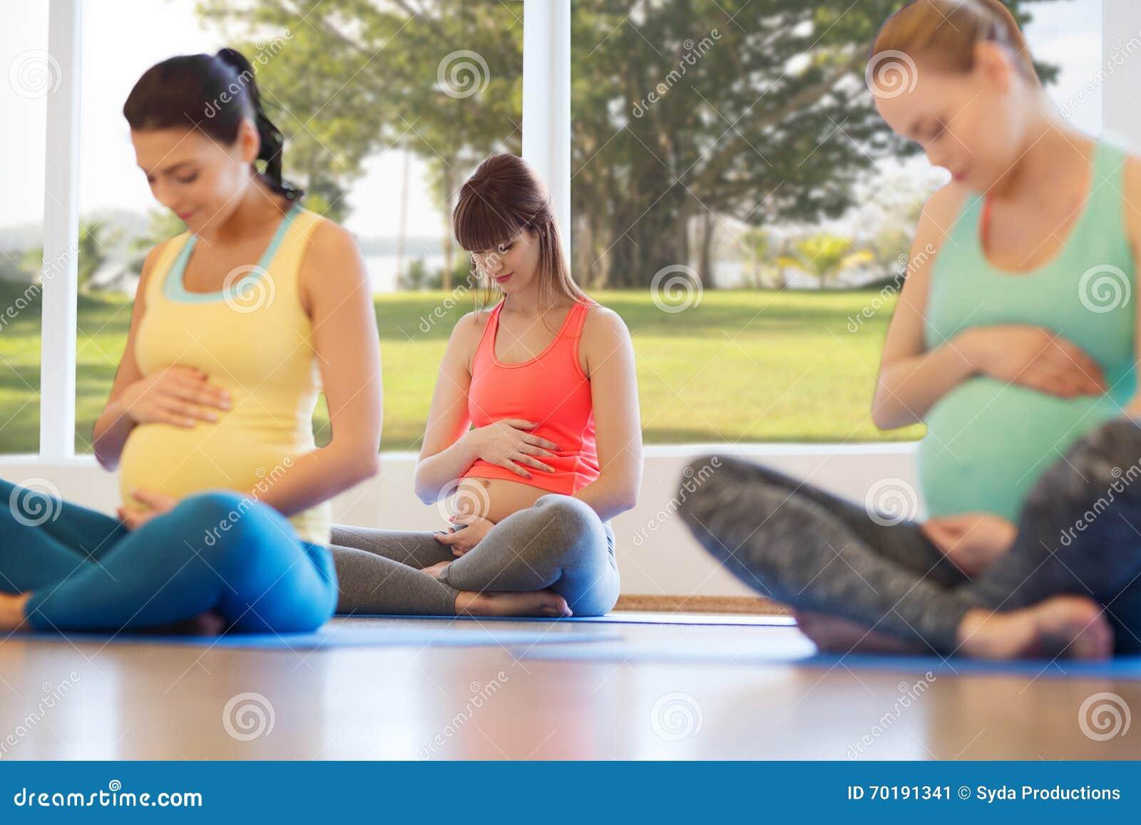 Lyckliga gravida kvinnor som övar yoga i idrottshall