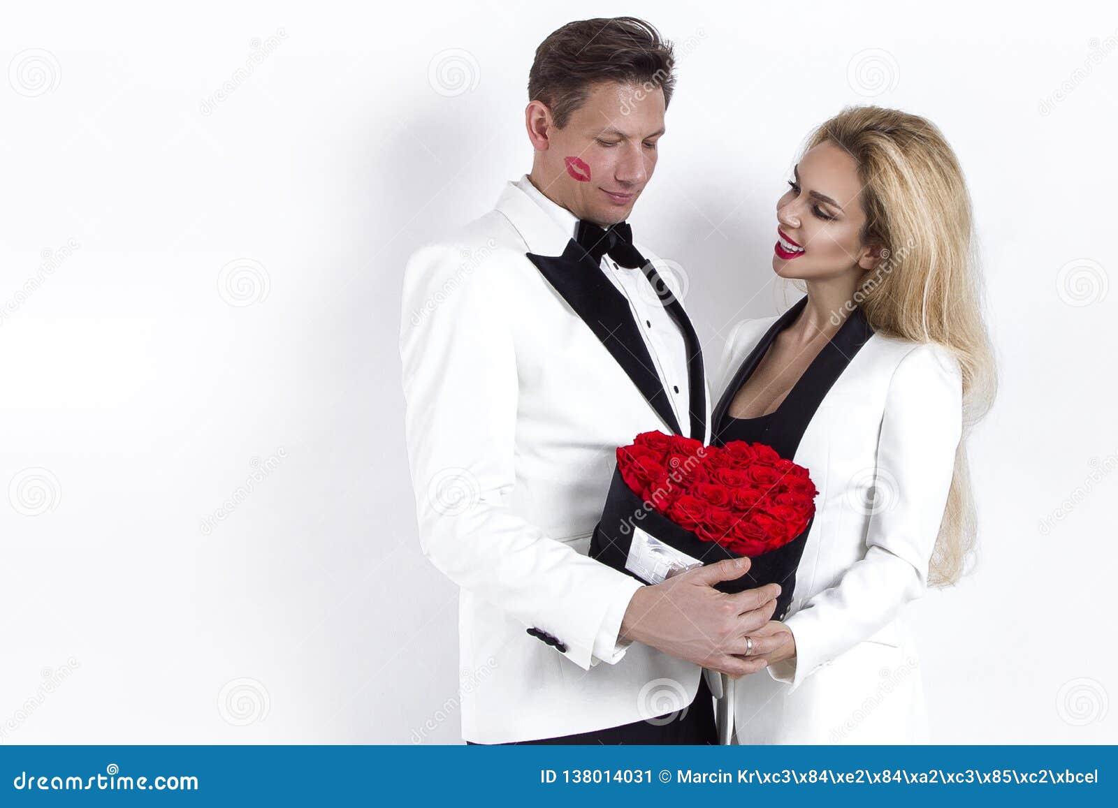 Lyckliga härliga par som poserar på vit bakgrund och rymmer blommaasken med röd hjärta Dag för valentin` som s gifta sig