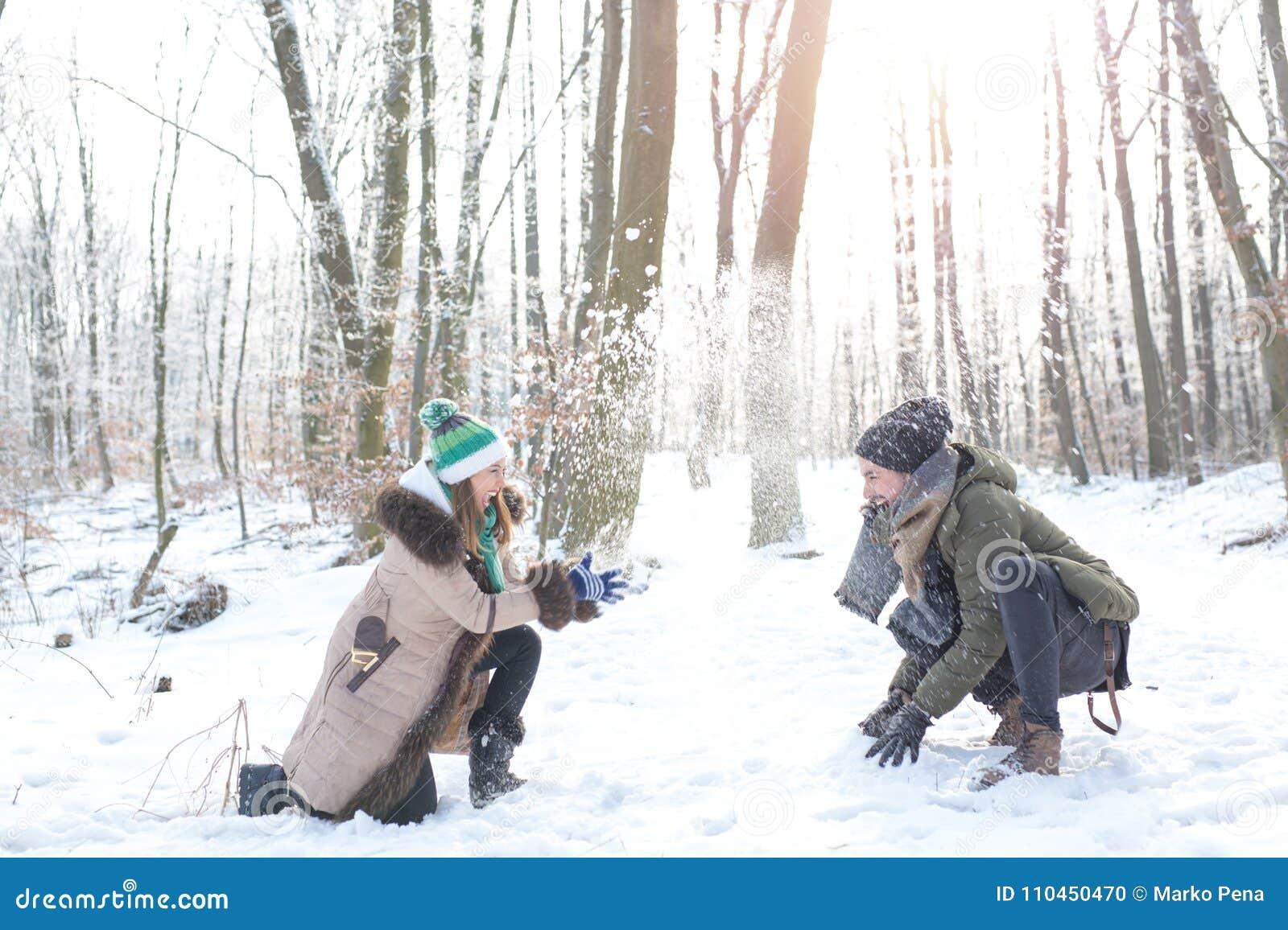 Lyckliga härliga par som spelar i snön