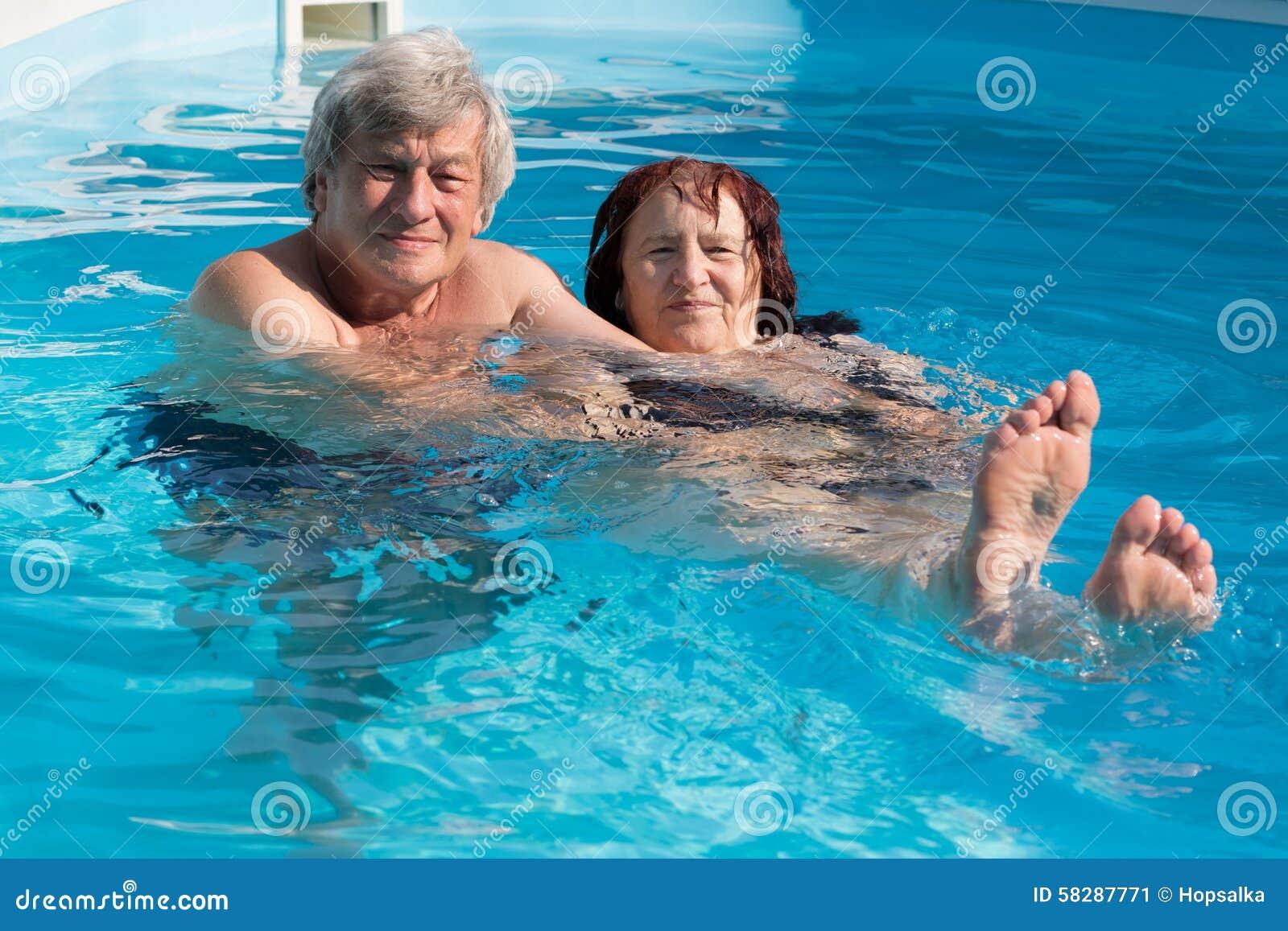Lyckliga höga par i en simbassäng