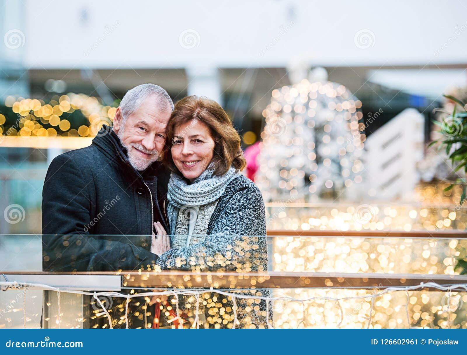 Lyckliga höga par som gör jul som tillsammans shoppar