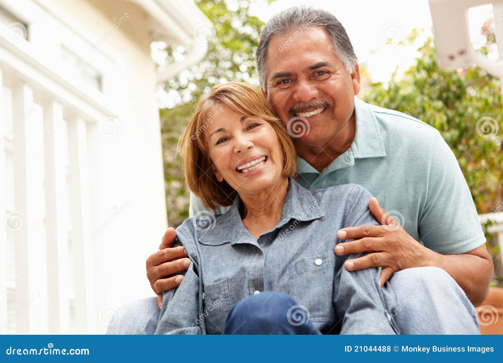 Lyckliga höga par som kopplar av i trädgård