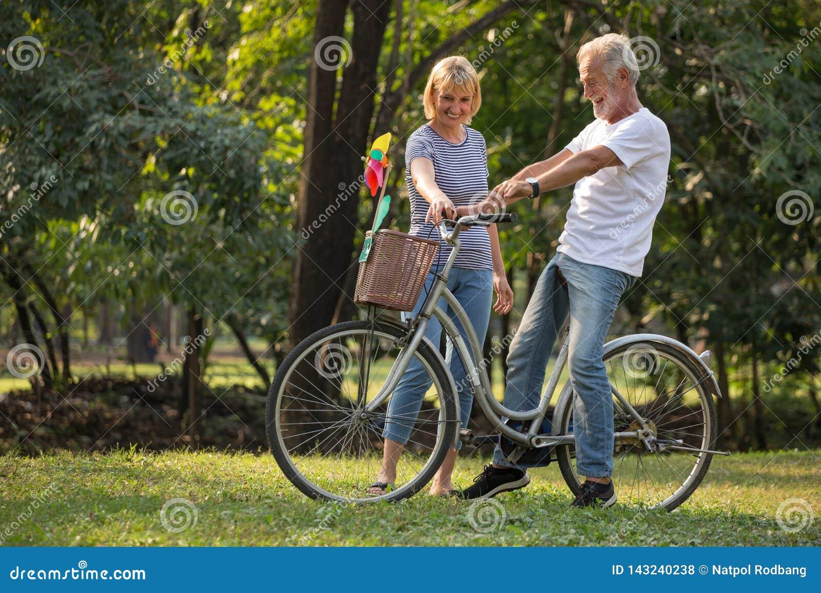 Lyckliga höga par som kopplar av på, parkerar att gå med cykeln och samtal tillsammans i morgontid gamla människor i hösten parke