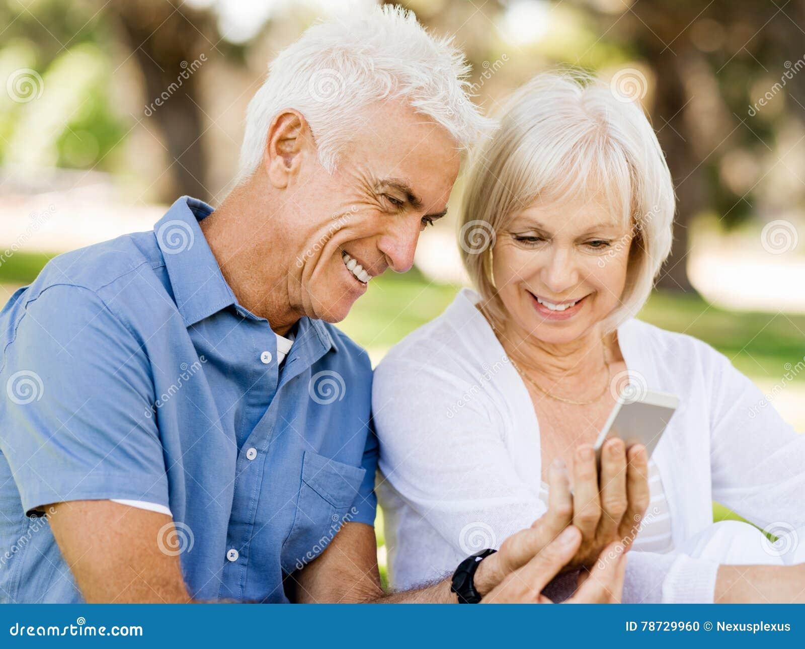 Lyckliga höga par som ser smartphonen