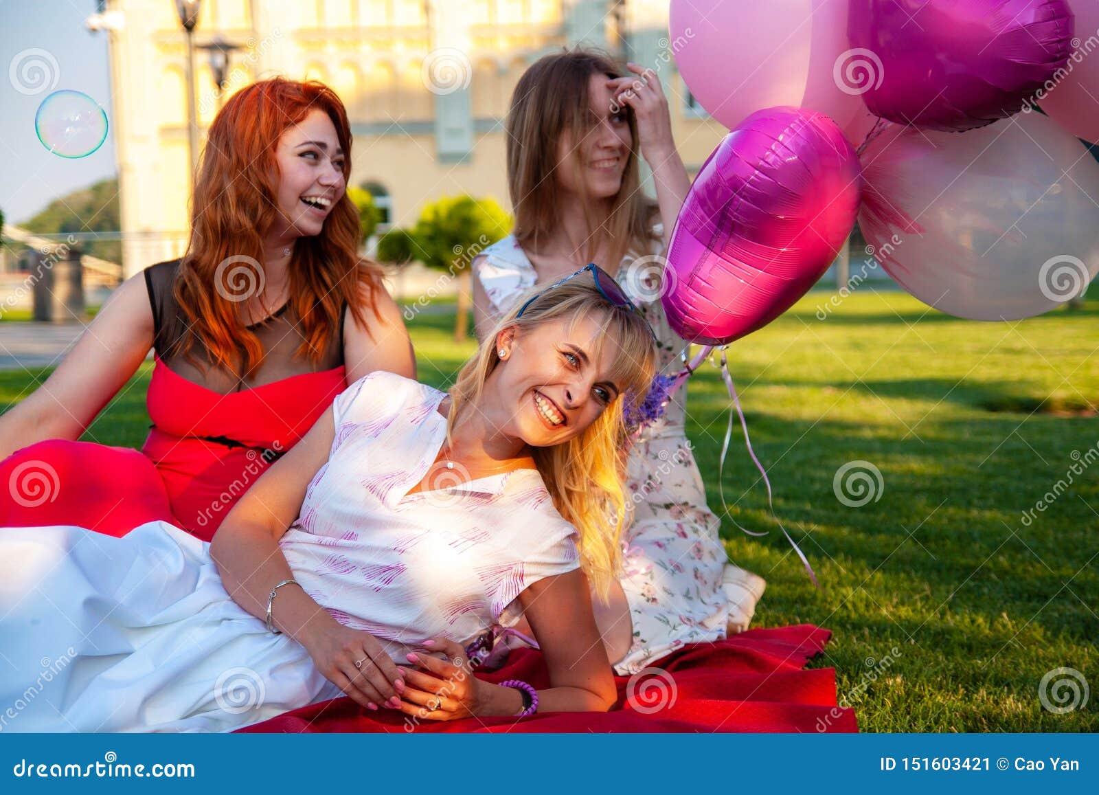 Lyckliga kvinnliga vänner som spelar och har gyckel i grönt gräs