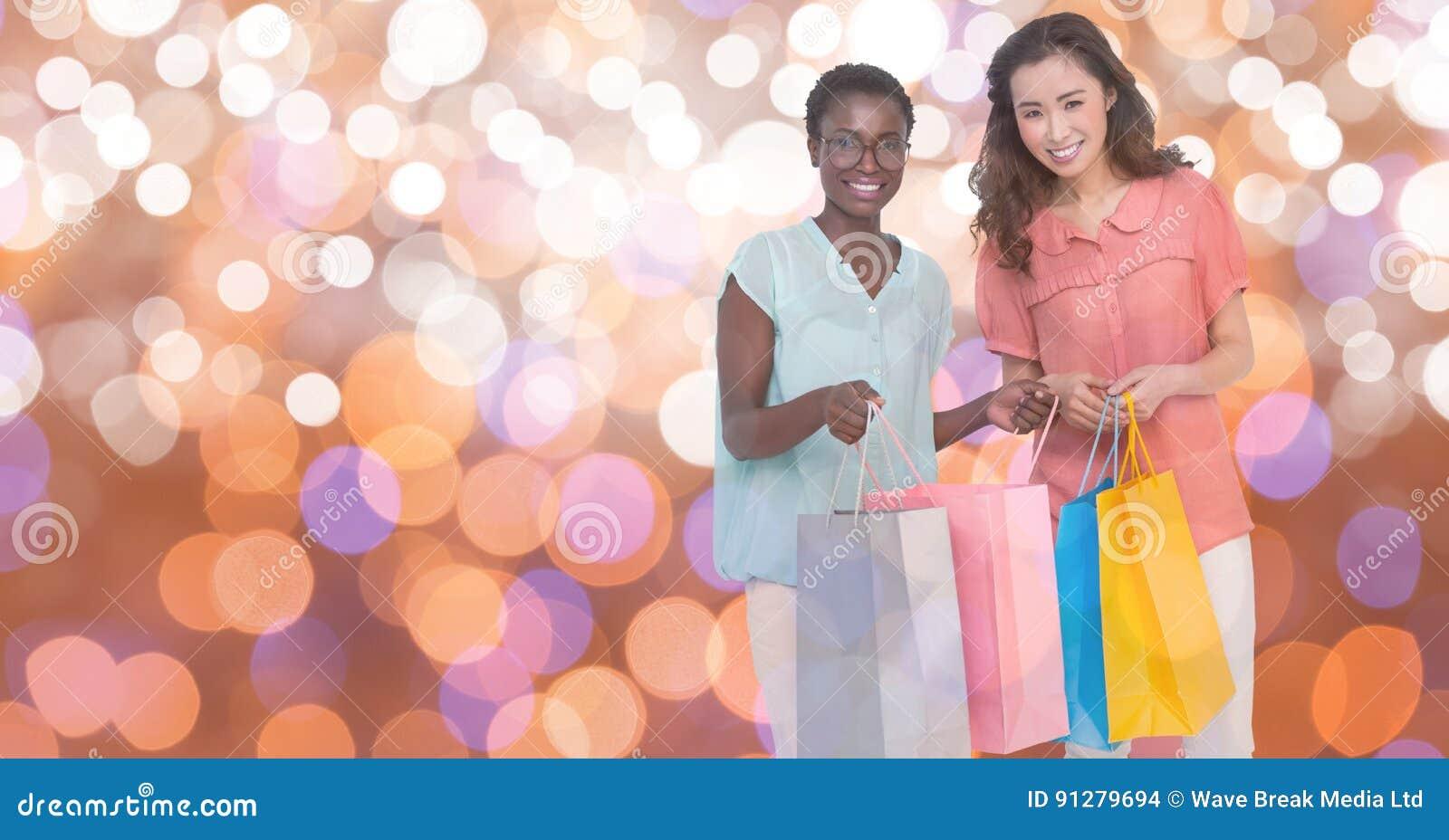 Lyckliga kvinnor som bär shoppingpåsar över bokeh