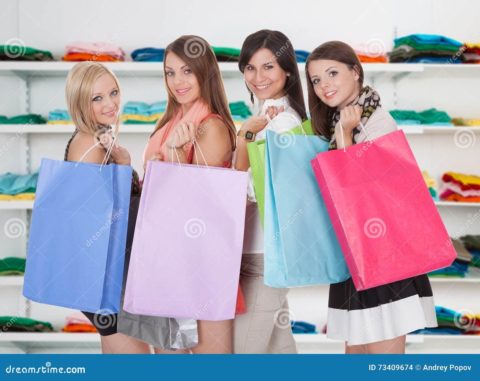 Lyckliga kvinnor som bär shoppingpåsar i lager