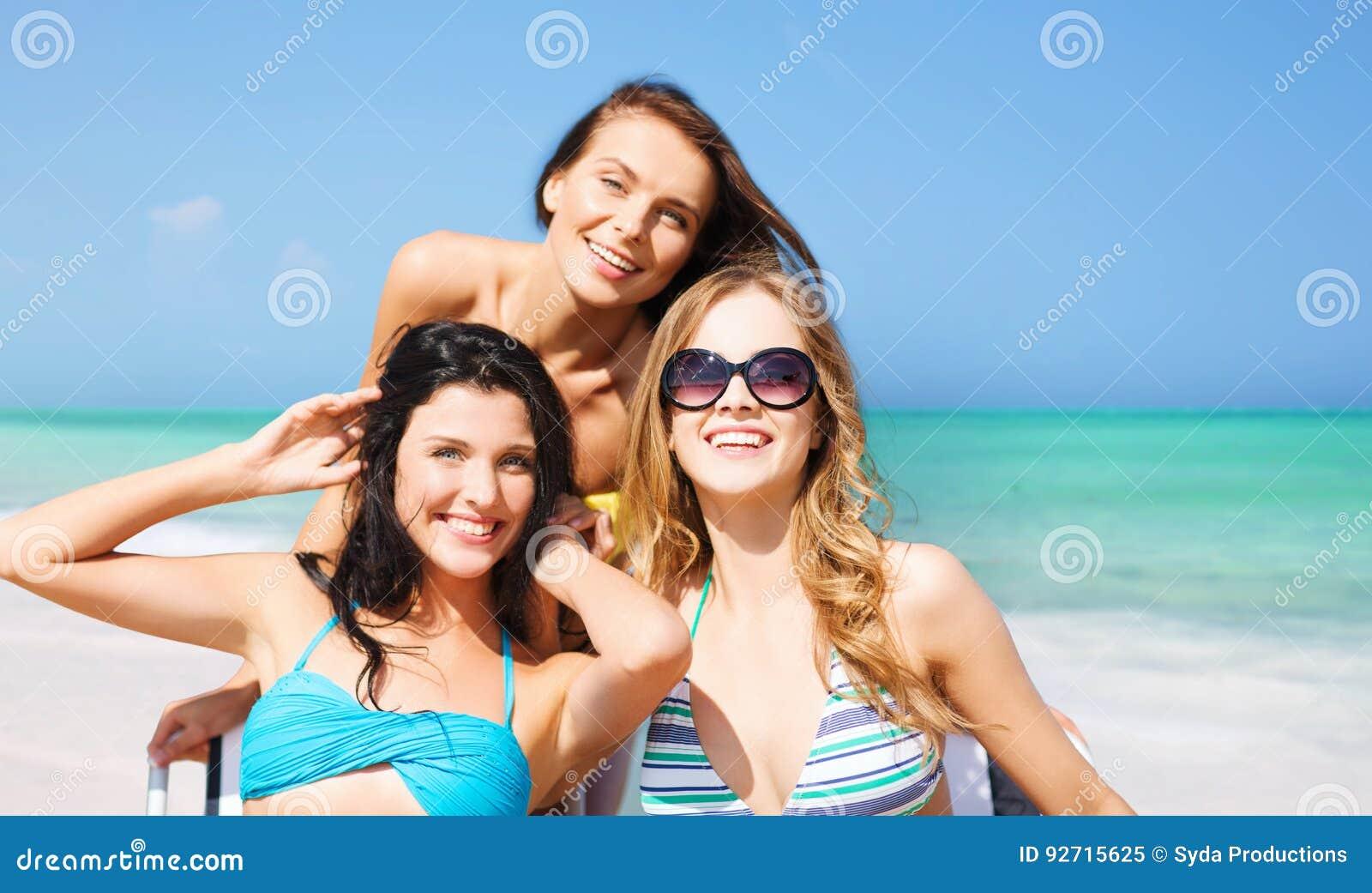 Lyckliga kvinnor som solbadar på stolar över sommarstranden