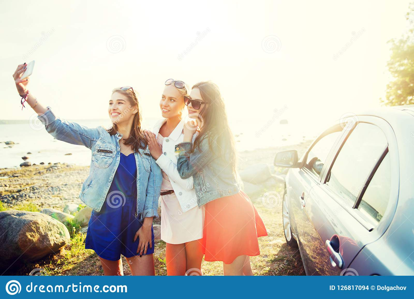 Lyckliga kvinnor som tar selfie nära bilen på sjösidan