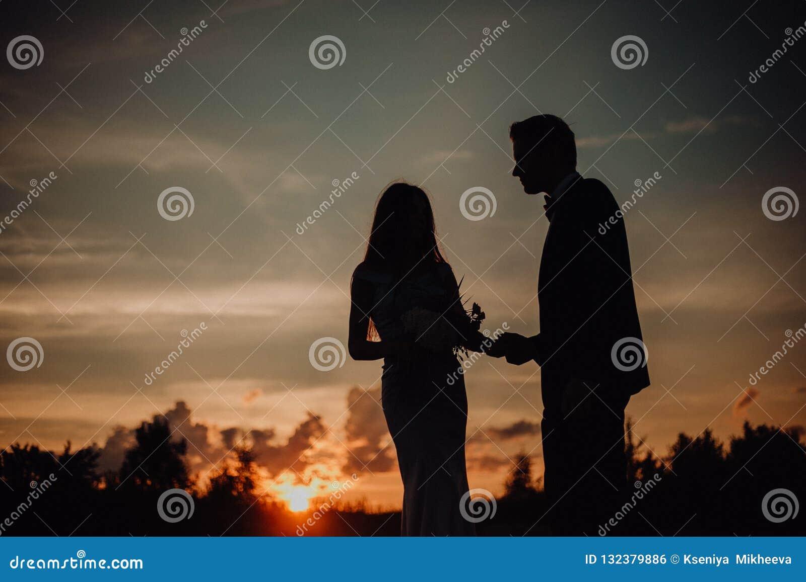 Lyckliga le par för kontur av den sexiga flickan för grabbkyss på sand i klassisk klänning träd och himmel på bakgrund