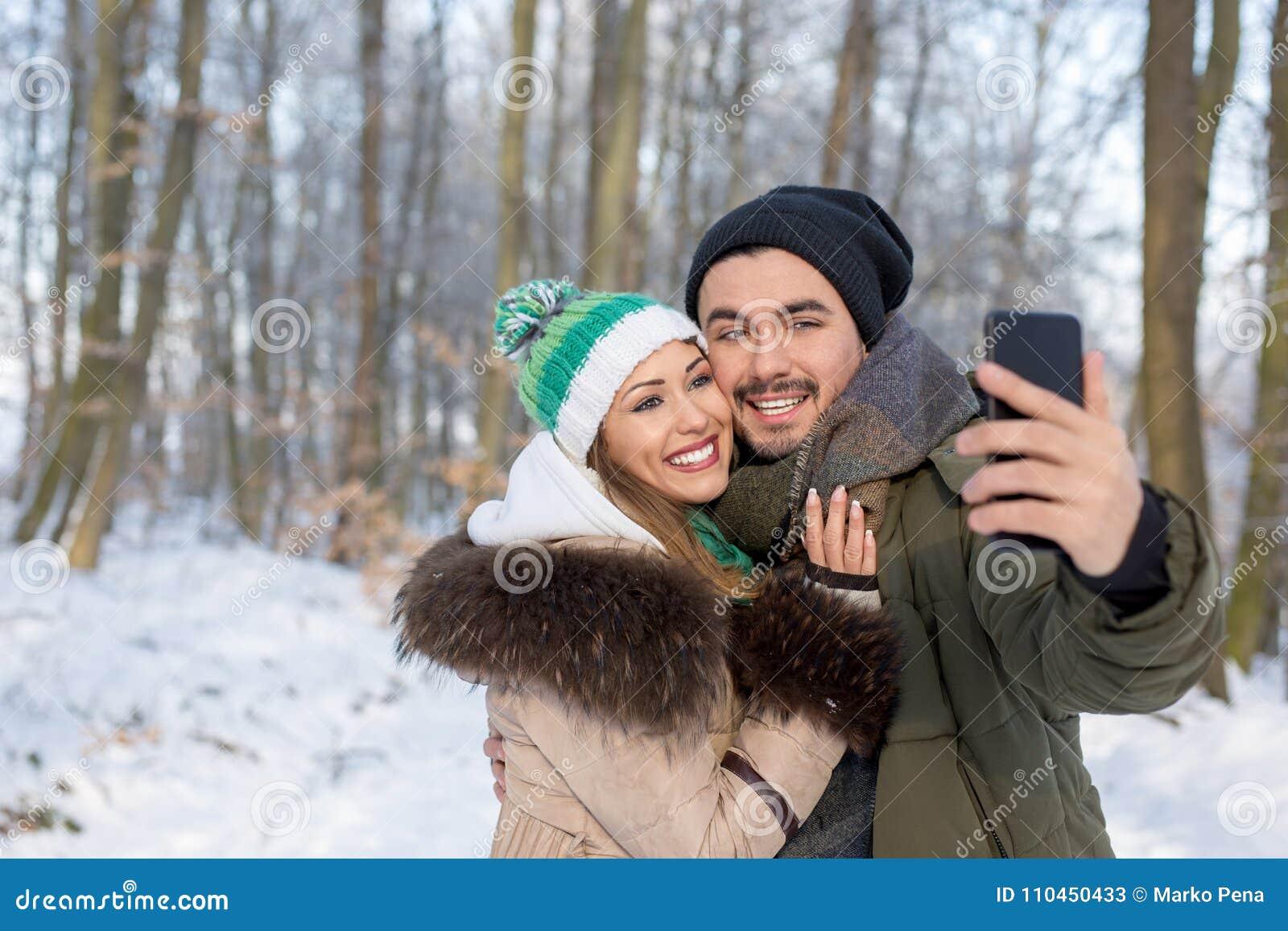 Lyckliga le par som tar en selfie i en vinterskog