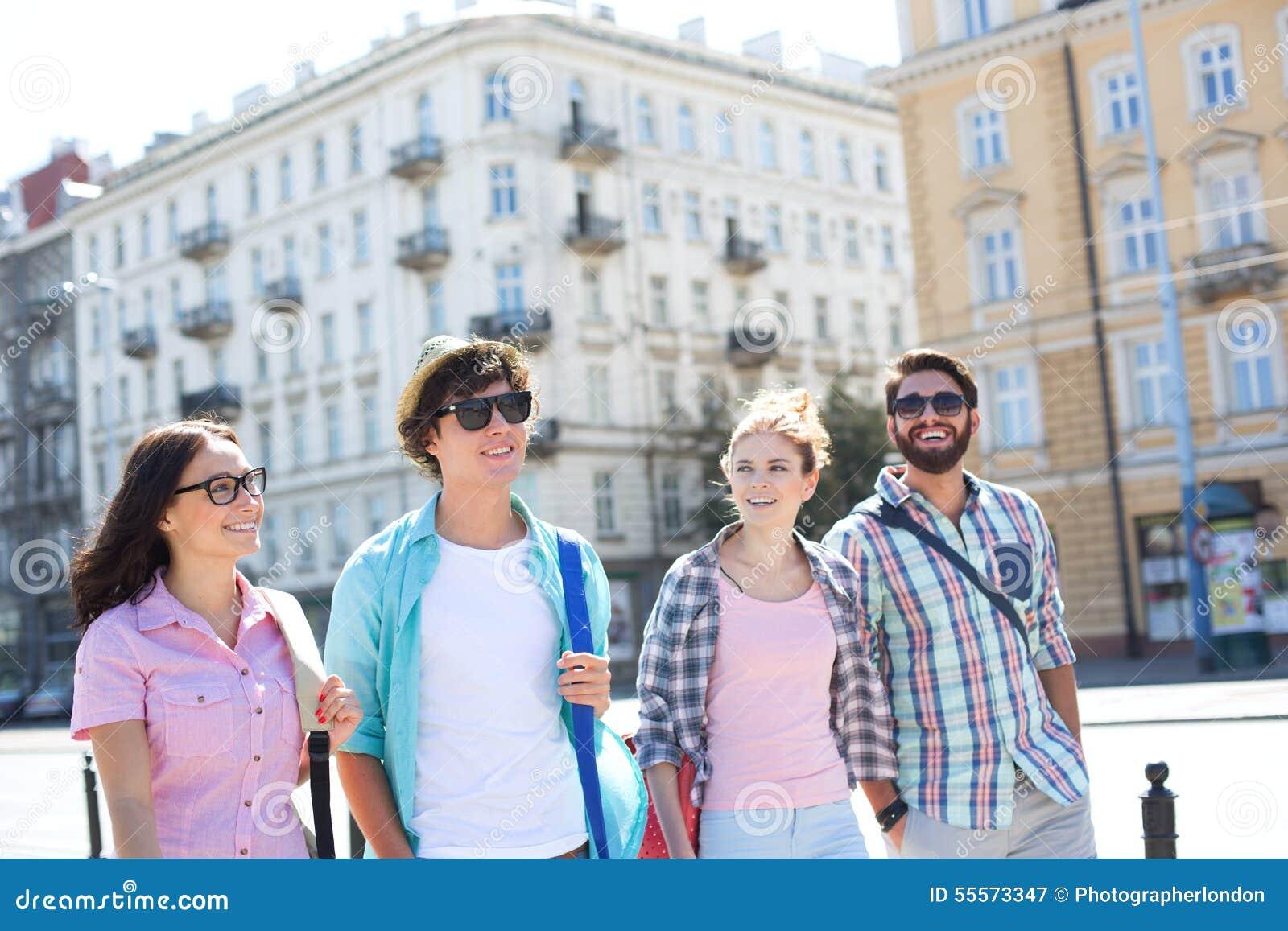 Lyckliga manliga och kvinnliga vänner som går på stadsgatan
