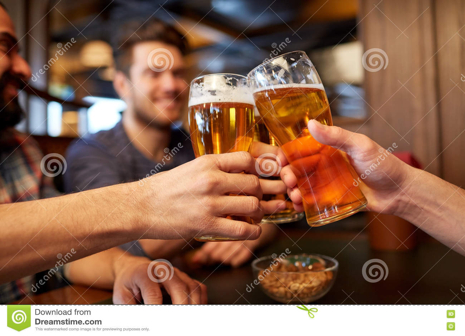 Lyckliga manliga vänner som dricker öl på stången eller baren