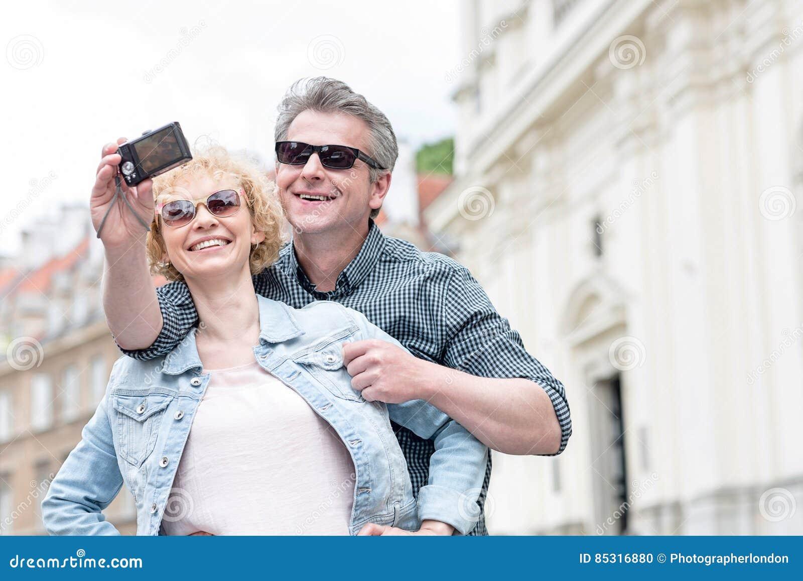 Lyckliga medelåldersa par i solglasögon som utomhus tar självståenden