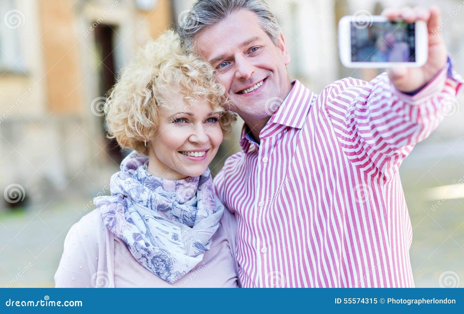 Lyckliga medelåldersa par som utomhus tar selfie till och med den smarta telefonen