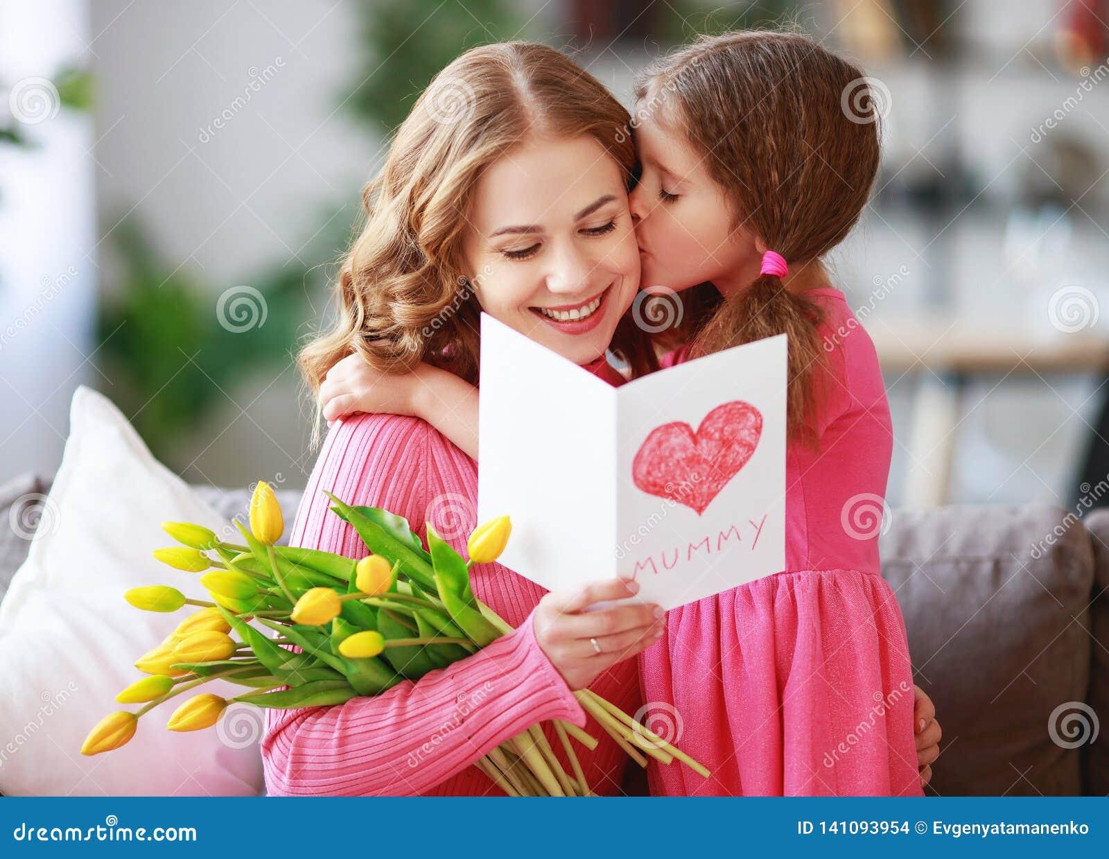 Lyckliga moders dag! barndottern ger modern en bukett av blommor till tulpan och vykortet