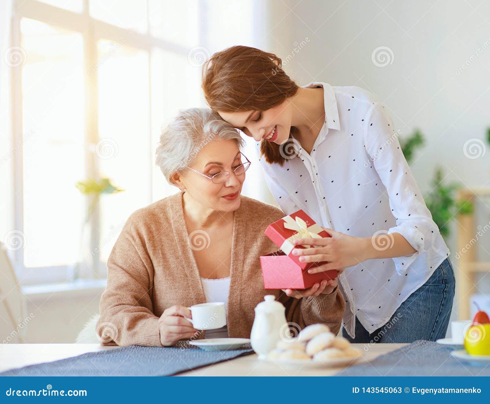 Lyckliga moders dag! den vuxna dottern ger gåvan och gratulerar en äldre moder på ferie