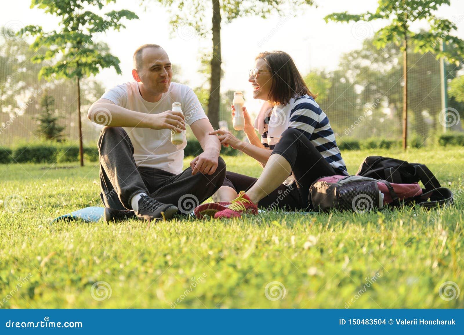 Lyckliga mogna par som sitter i, parkerar på matt kondition och att vila dricka yoghurt efter sportövningar