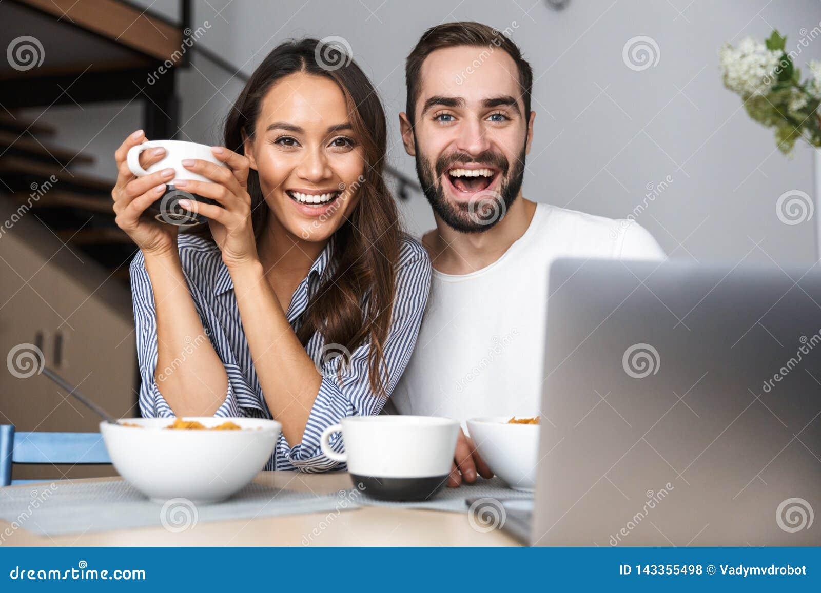 Lyckliga multietniska par som har frukosten