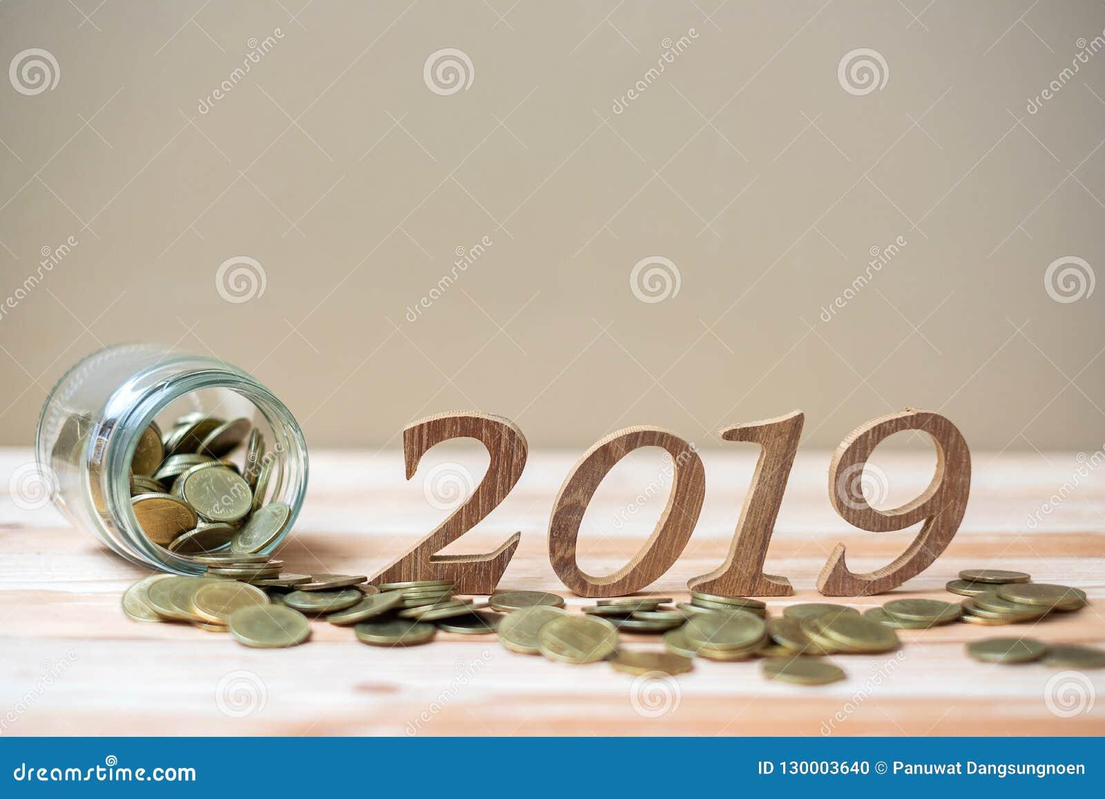 2019 lyckliga nya år med bunten för guld- mynt och tränummer på tabellen affär investering, avgångplanläggning, finans, besparing