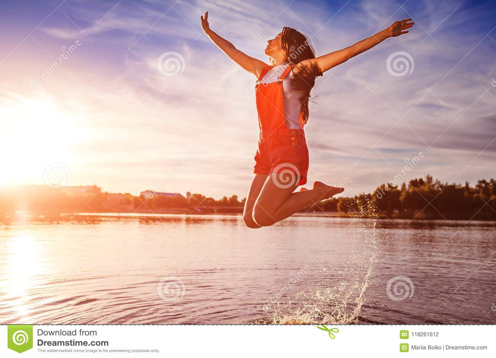 Lyckliga och fria banhoppning för ung kvinna och lyftaarmar på flodbanken Frihet aktiv livsstil