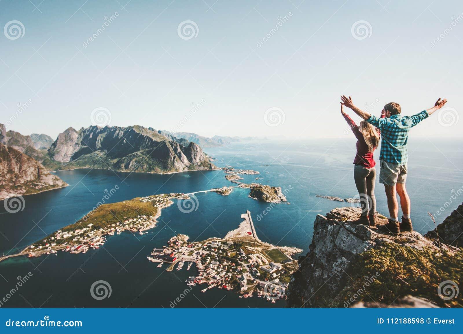 Lyckliga par älskar och reser lyftta händer på klippan