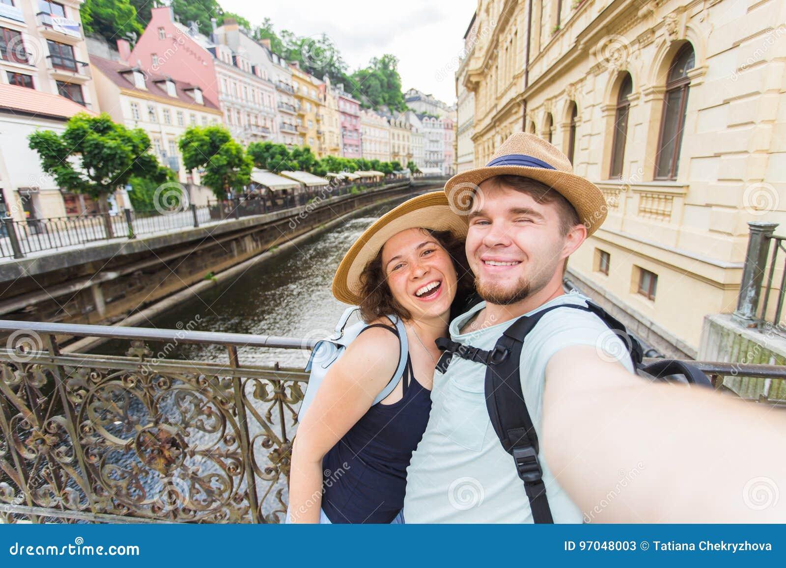 Lyckliga par, attraktiv kvinna och man som går i stad och tycker om romans Vänner som gör selfie och att le turister
