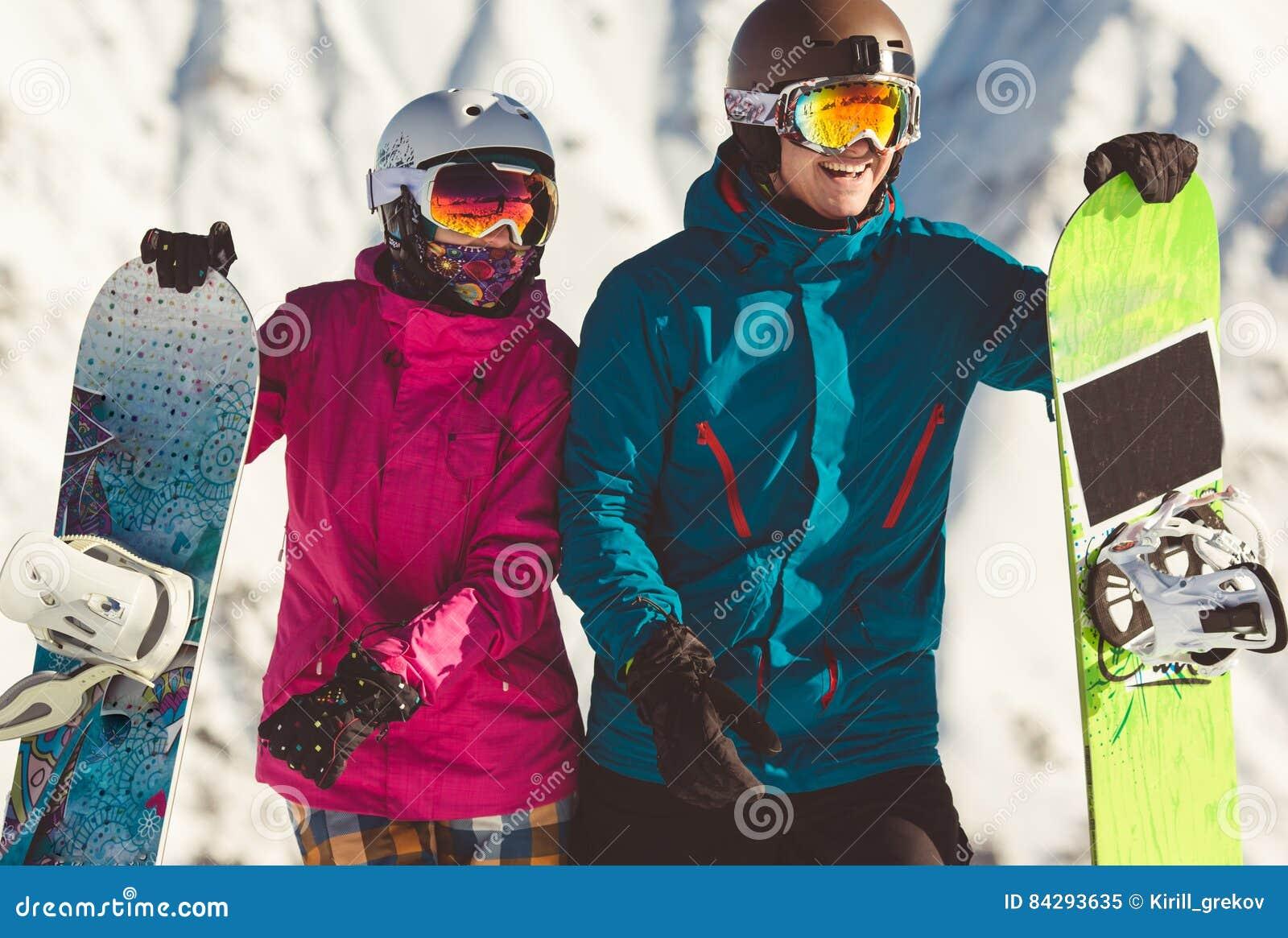 Lyckliga par av snowboarders i de alpina bergen