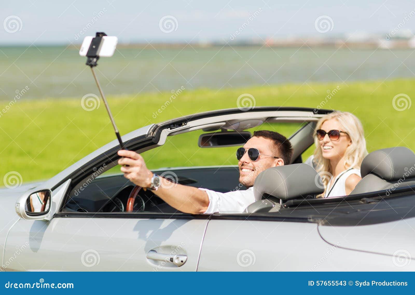 Lyckliga par i bilen som tar selfie med smartphonen