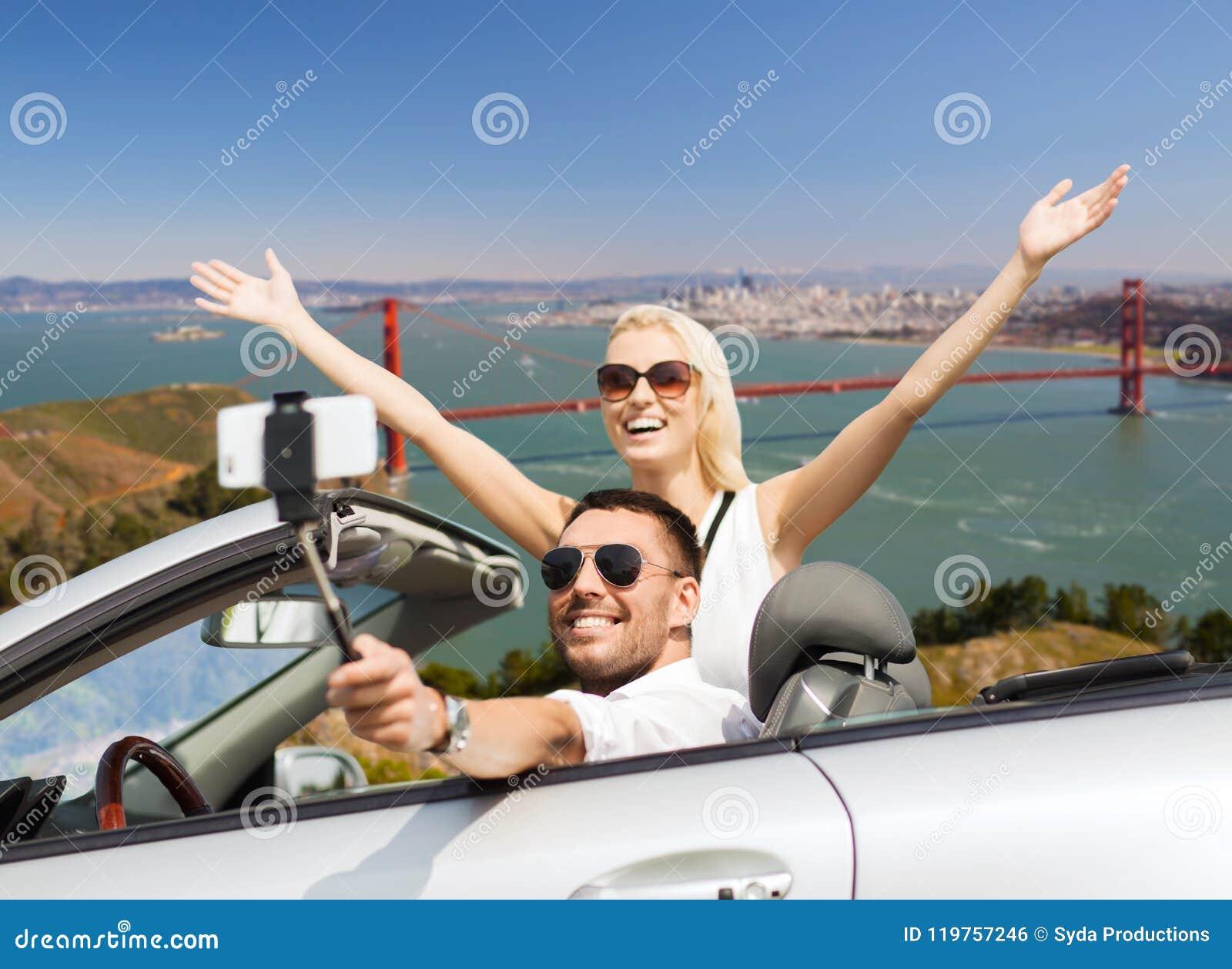 Lyckliga par i bilen som tar selfie vid smartphonen