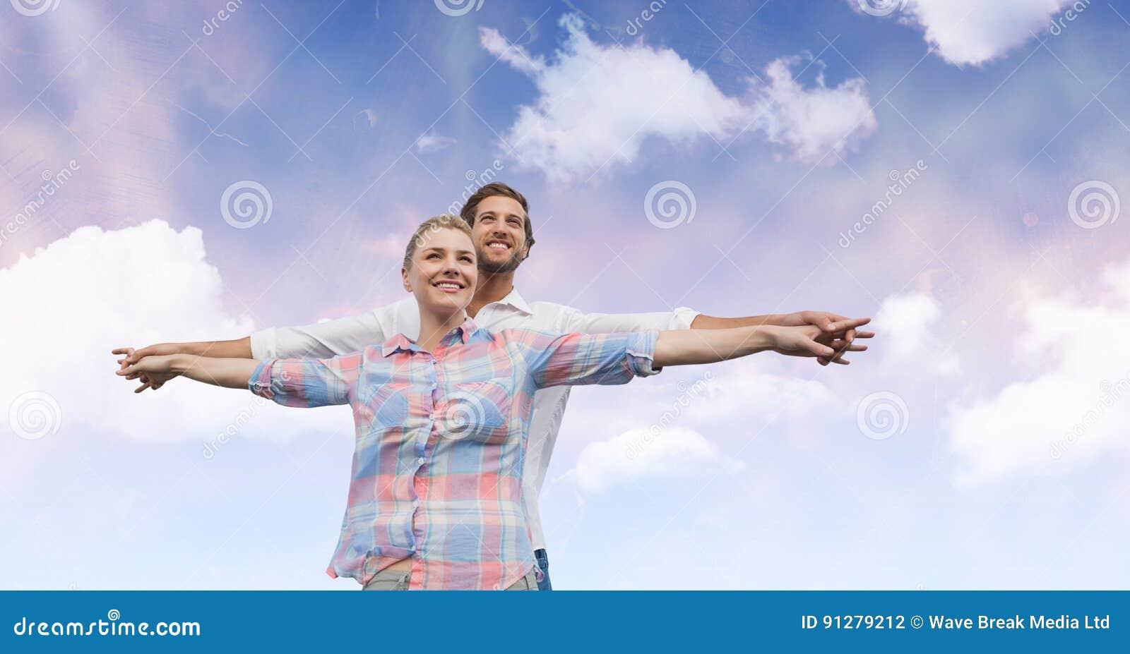 Lyckliga par med armar som är utsträckta mot himmel