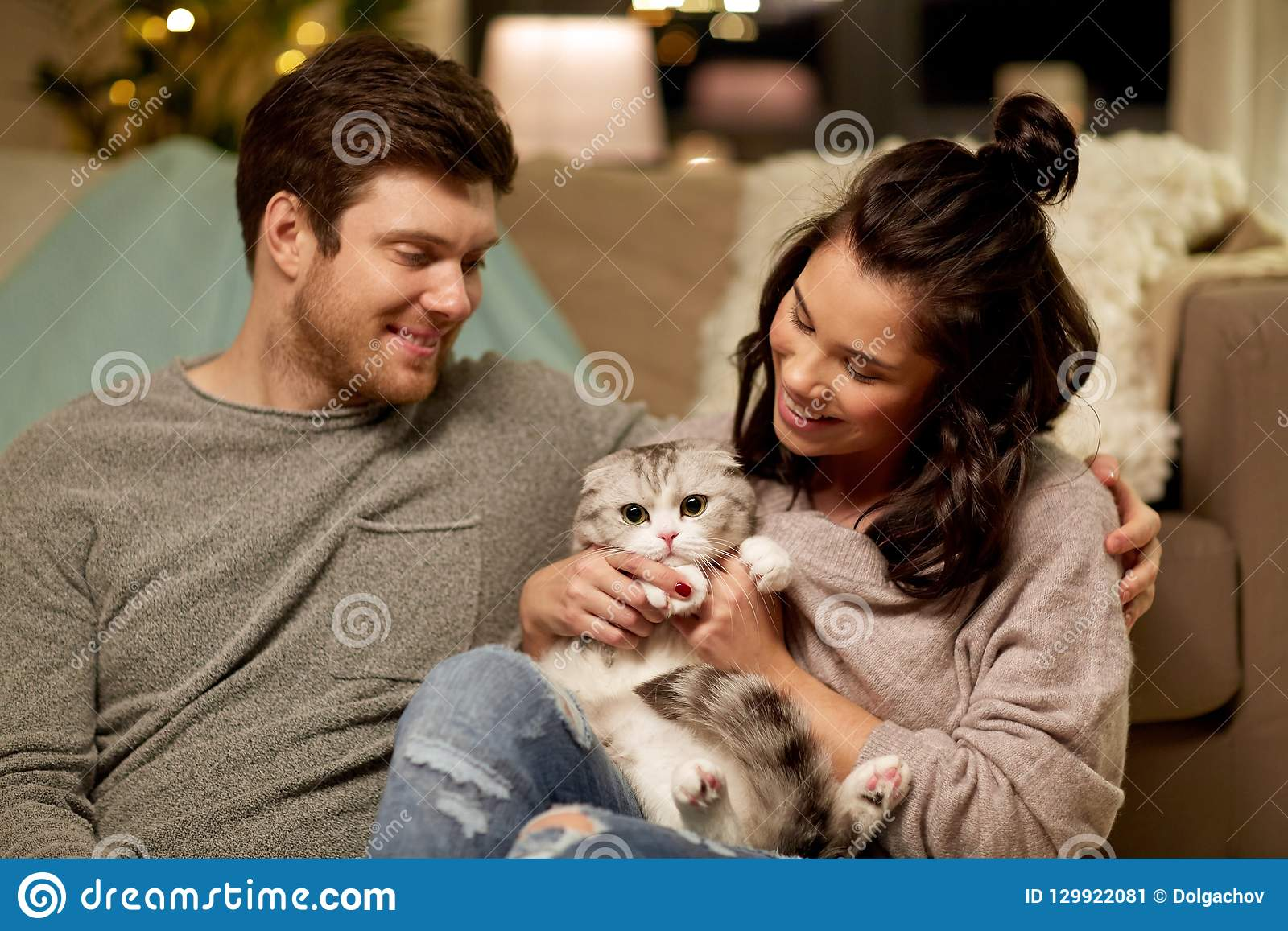 Lyckliga par med den hemmastadda katten