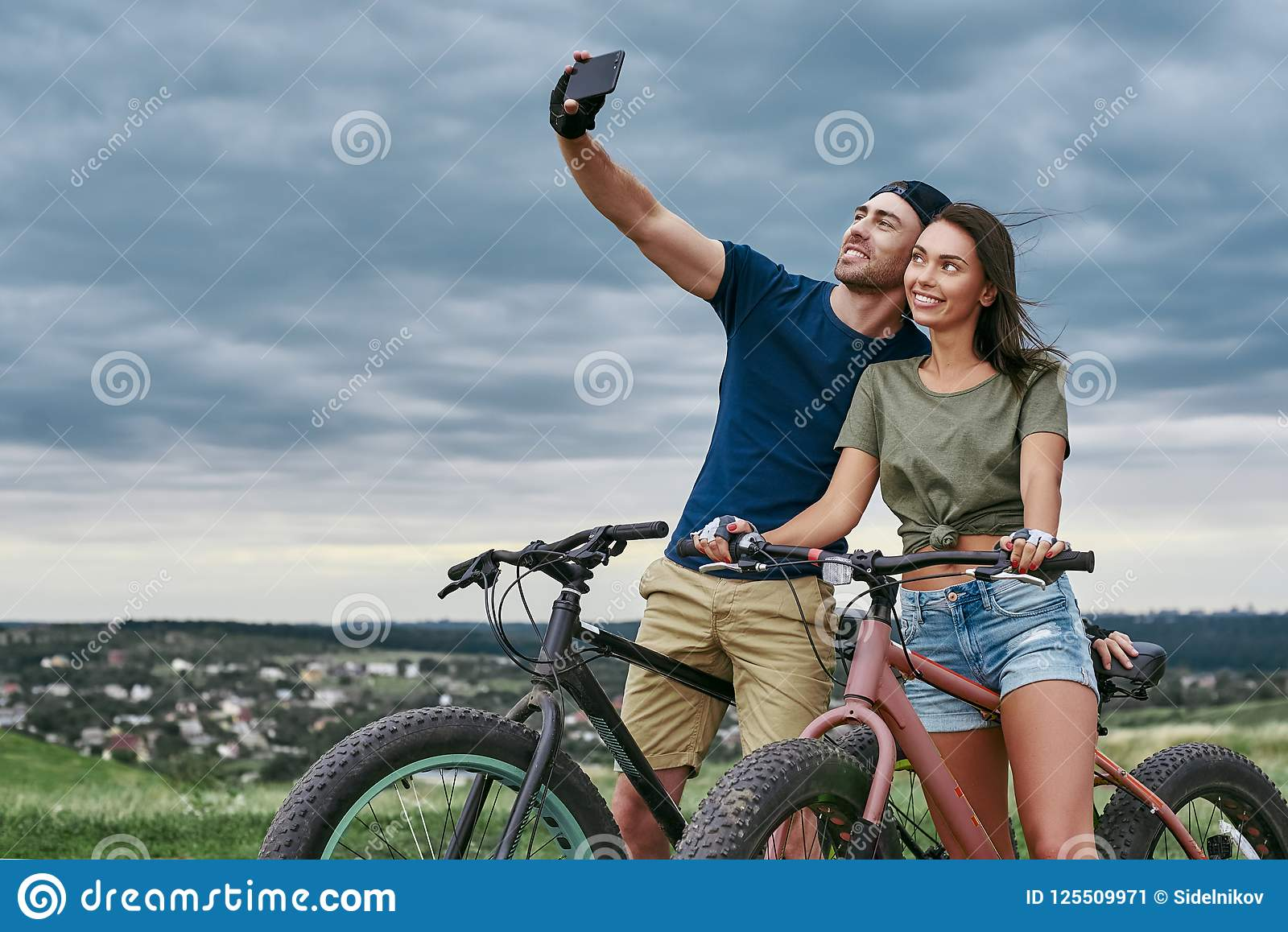 Lyckliga par med fatbikes som utomhus tar selfie vid smartphonen