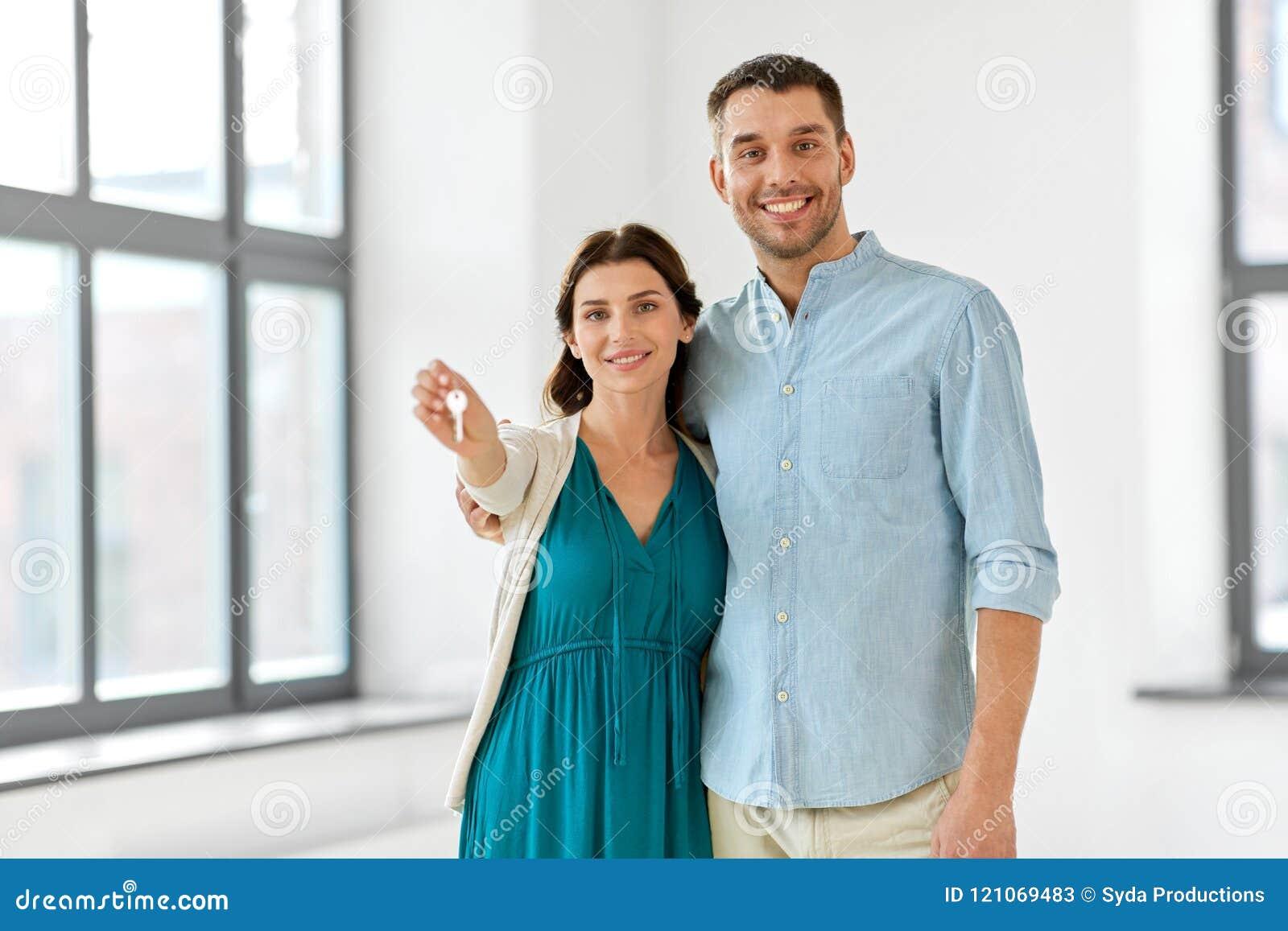 Lyckliga par med tangenter av det nya hemmet