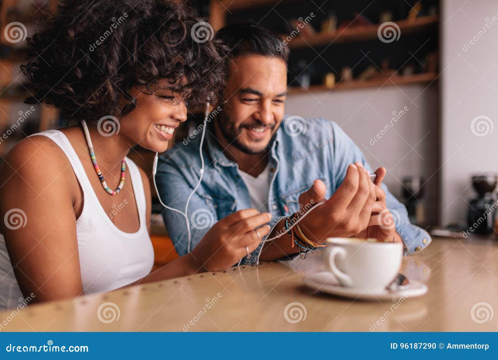 Lyckliga par på kafét som har video pratstund på mobiltelefonen